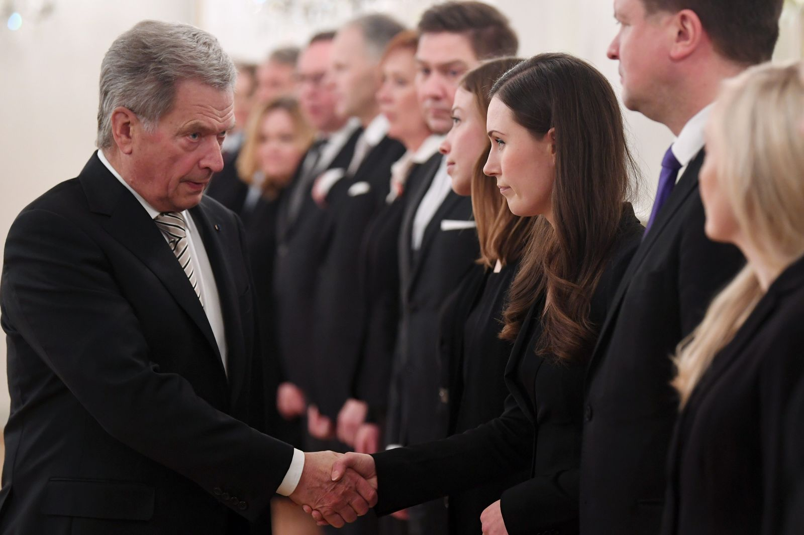 Finland's President Sauli Niinisto, left, and Prime Minister Sanna Marin shake hands to welcome the new government of Finland in Helsinki, Finland on Tuesday Dec. 10, 2019. Finland's parliament chose Sanna Marin as the country's new prime minister Tuesday, making the 34-year-old the world's youngest sitting head of government. (Jussi Nukari/Lehtikuva via AP)