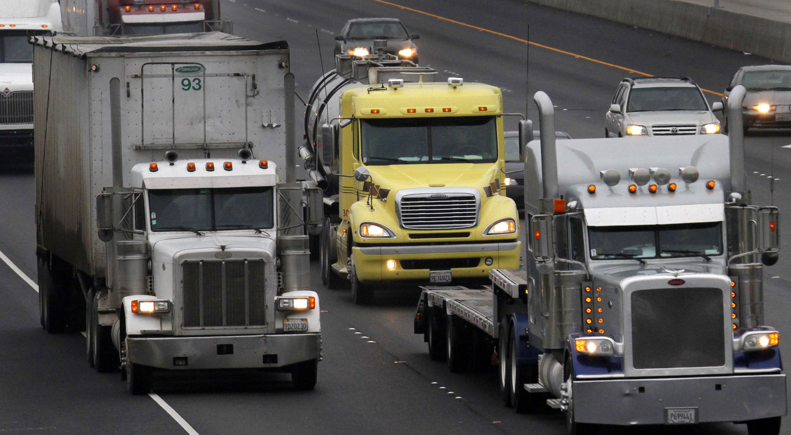 FILE - In this Dec. 17, 2010 file photo, trucks make their way in Livermore, Calif. A new study released Monday, March 11, 2019, says African-Americans and Hispanics breathe in far more deadly air pollution than they are responsible for making.   (AP Photo/Ben Margot, File)