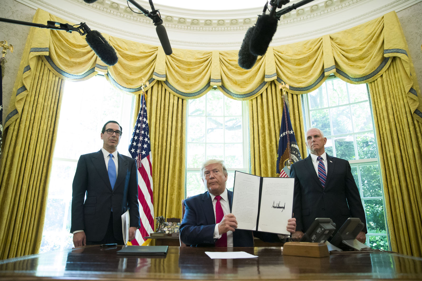 FILE - In this June 24, 2019, file photo, President Donald Trump holds up a signed executive order to increase sanctions on Iran, in the Oval Office of the White House in Washington, with Treasury Secretary Steven Mnuchin, left, and Vice President Mike Pence. Trump is now three for three. Each year of his presidency, he has issued more executive orders than did former President Barack Obama during the same time-span. (AP Photo/Alex Brandon, File)