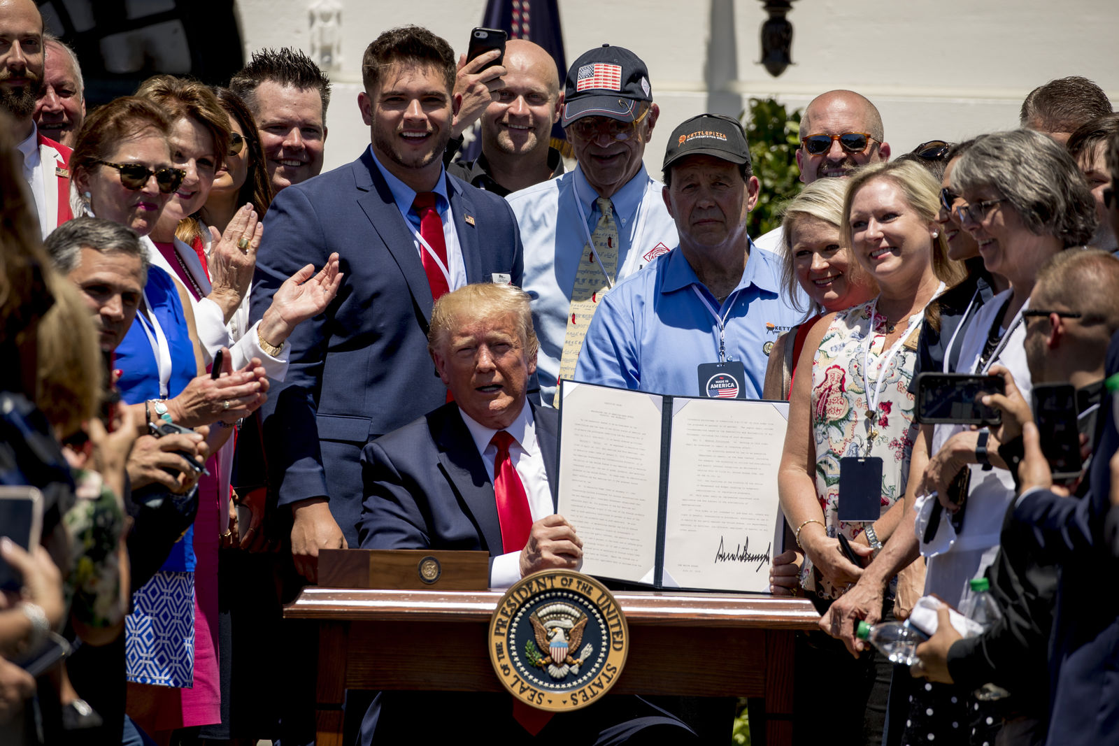 FILE - In this July 15, 2019, file photo, company representatives invited to the White House stand next to President Donald Trump as he holds up an executive order after he signs it during a Made in America showcase on the South Lawn in Washington. Trump is now three for three. Each year of his presidency, he has issued more executive orders than did former President Barack Obama during the same time-span. (AP Photo/Andrew Harnik, File)