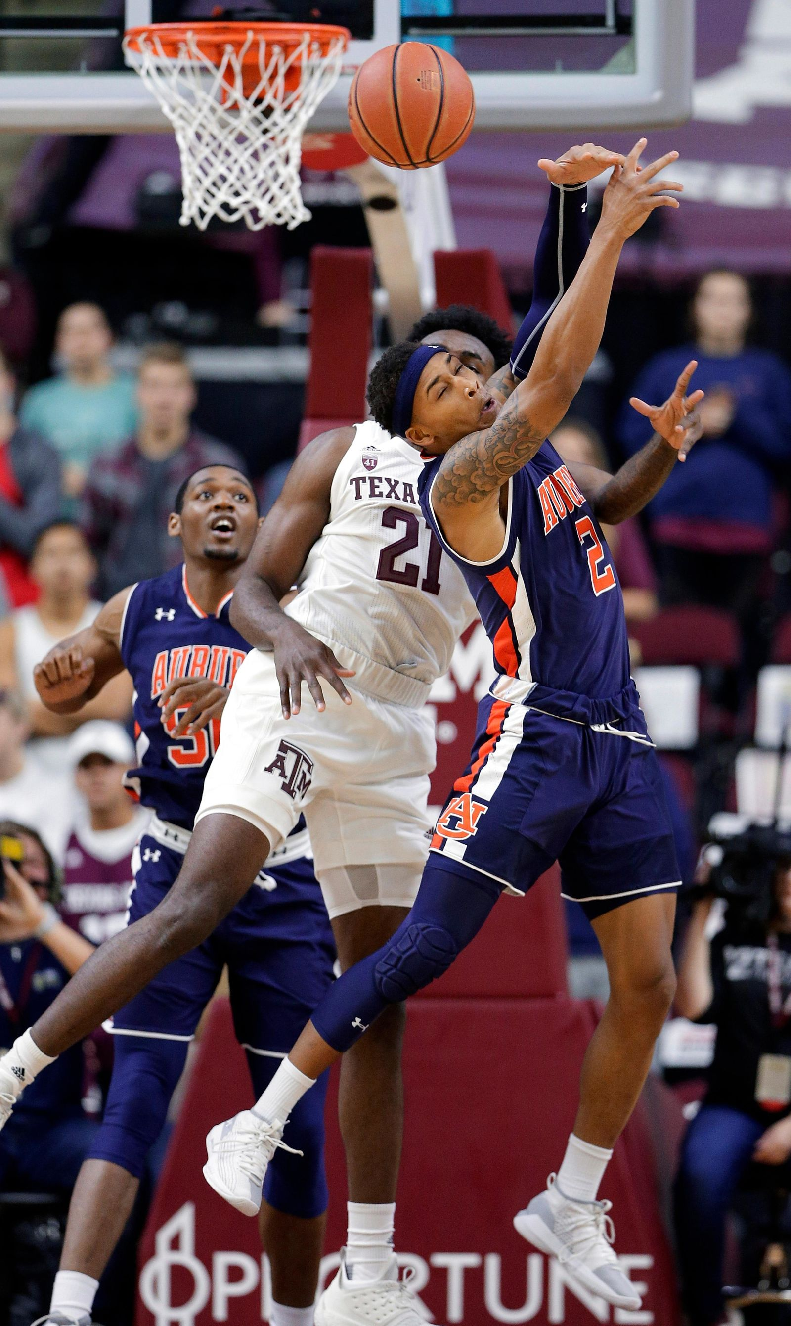Auburn guard Bryce Brown (2) loses a rebound in front of Texas A&M forward Christian Mekowulu (21) as Auburn center Austin Wiley, back, looks on during the first half of an NCAA college basketball game, Wednesday, Jan. 16, 2019, in College Station, Texas. (AP Photo/Michael Wyke)