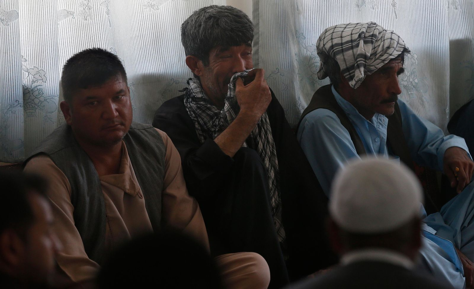 Men mourn for victims of the Dubai City wedding hall bombing during a memorial service at a mosque in Kabul, Afghanistan, Tuesday, Aug. 20, 2019. Hundreds of people have gathered in mosques in Afghanistan's capital for memorials for scores of people killed in a horrific suicide bombing at a Kabul wedding over the weekend. (AP Photo/Rafiq Maqbool)