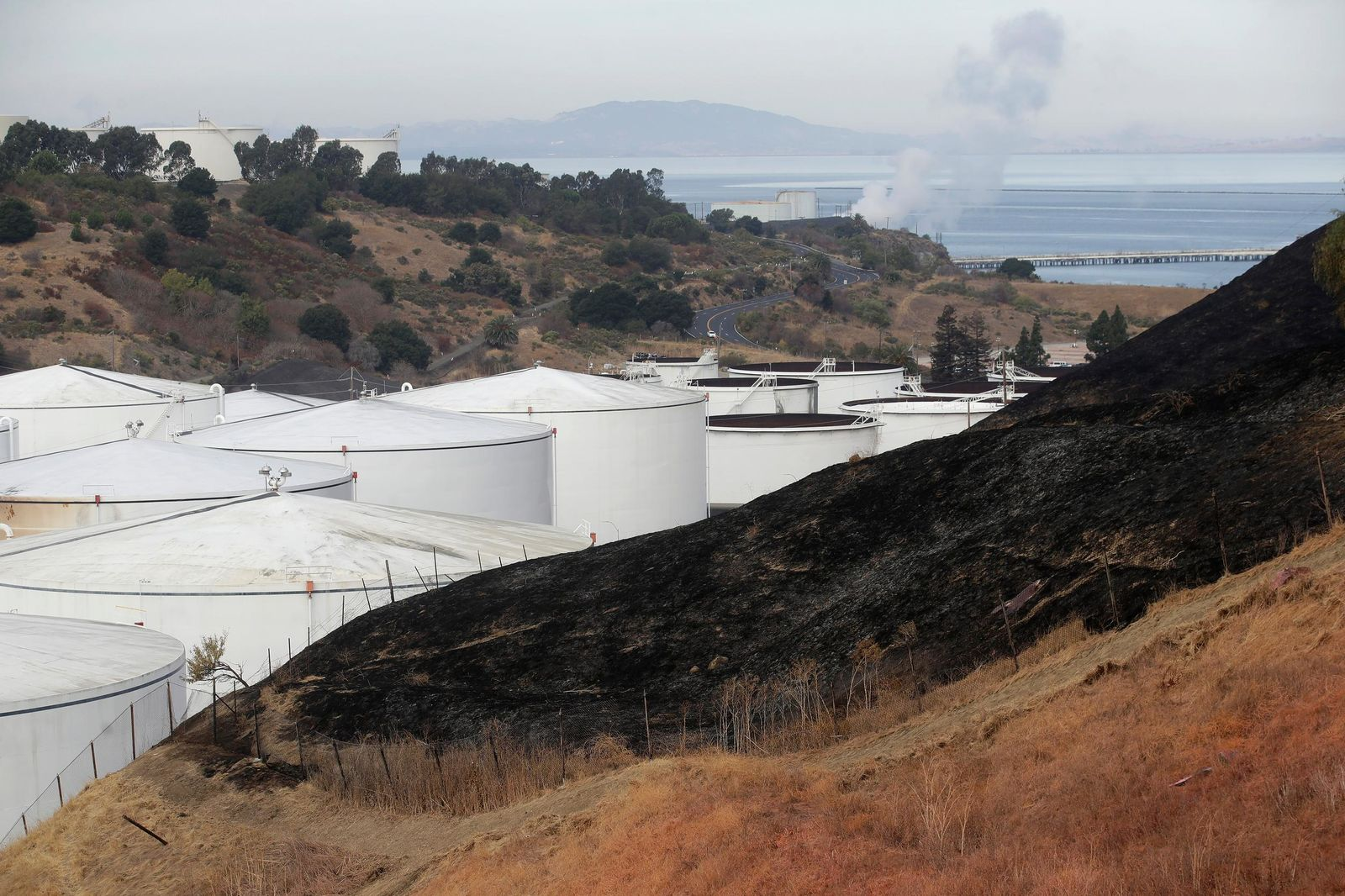 A burned hillside is shown from a Tuesday fire at NuStar Energy fuel storage facility in Crockett, Calif., Wednesday, Oct. 16, 2019. Officials were trying to determine Wednesday if a 4.5 magnitude earthquake triggered an explosion at the fuel storage facility in the San Francisco Bay Area that started a fire and trapped thousands in their homes for hours because of potentially unhealthy air. (AP Photo/Jeff Chiu)