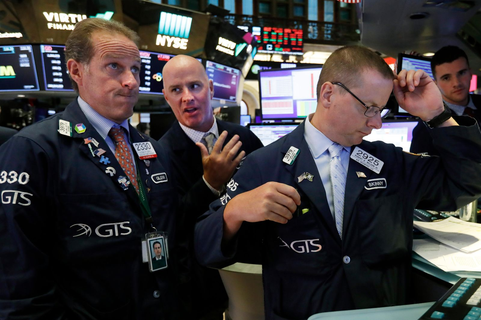 Specialists Glenn Carell, left, John 'Hara, center, and Robert Nelson, gather at a trading post on the floor of the New York Stock Exchange, Wednesday, Aug. 14, 2019.{ } (AP Photo/Richard Drew)