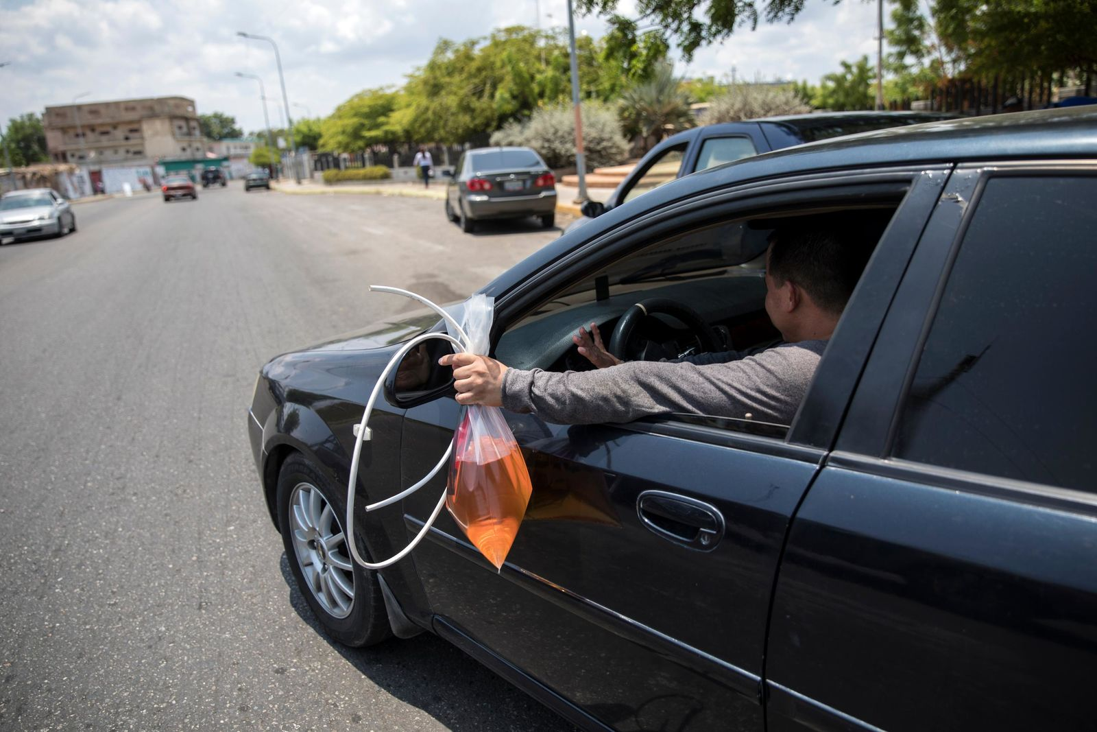 A man leaves a gas station with extra gasoline in a bag, after filling his tank with gas that cost him extra money but saved him waiting in a longer line in Cabimas, Venezuela, Saturday, May 18, 2019. (AP Photo/Rodrigo Abd)