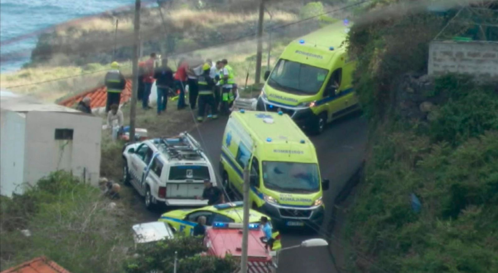 In this image from video, emergency services attend the scene after a tour bus crashed at Canico, on Portugal's Madeira Island, Wednesday April 17, 2019 (TVI via AP)