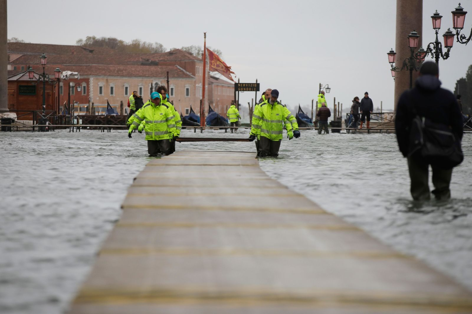 Municipality workers carry wooden boards to make a trestle bridge in a flooded St. Mark's Square at Venice, Italy, Friday, Nov. 15, 2019. (AP Photo/Luca Bruno)