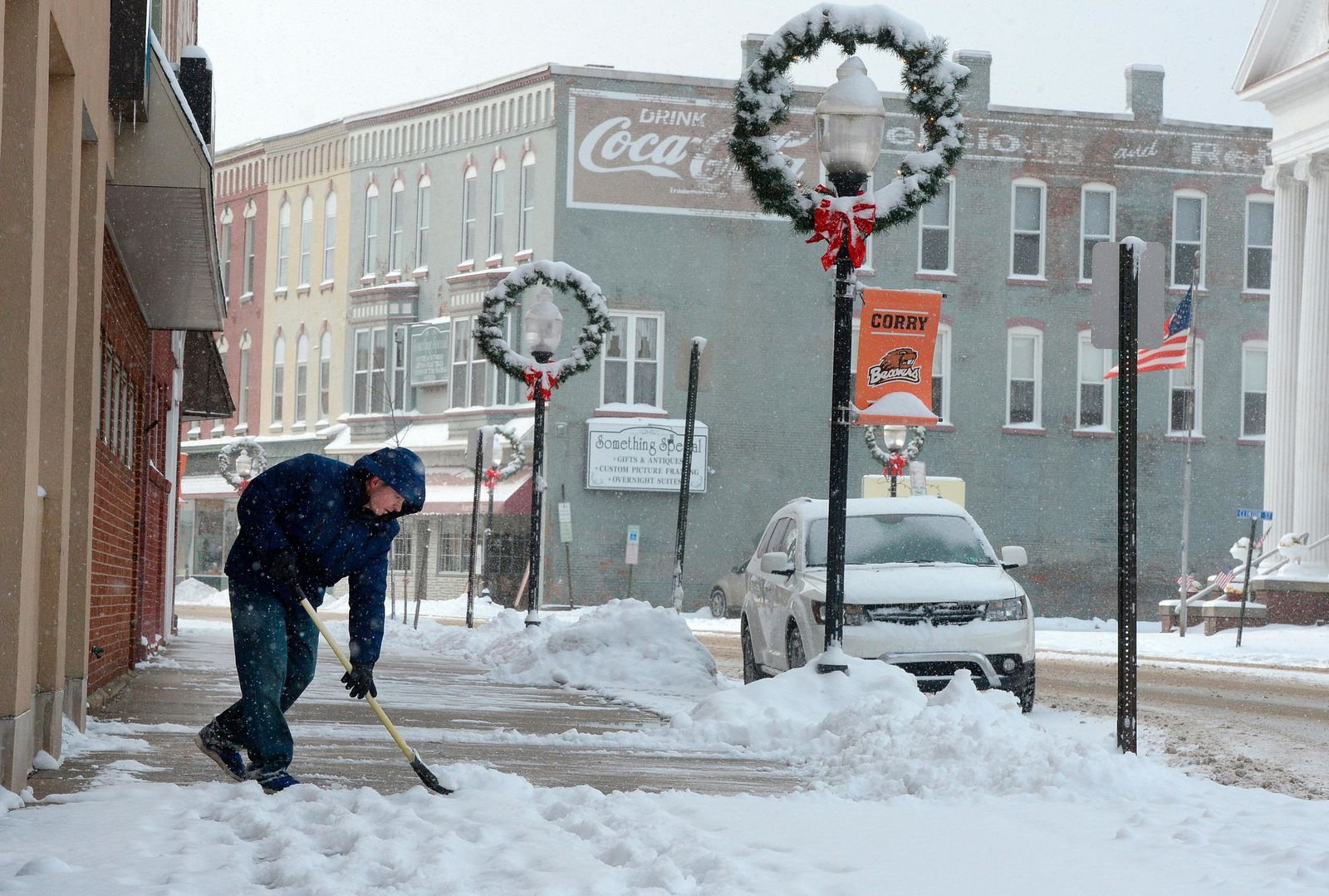 Ben Barney shovels the sidewalk on North Center Street in downtown Corry, Pennsylvania on Tuesday, Nov. 12, 2019. Erie and Crawford counties were under a winter storm warning from the National Weather Service in Cleveland. (Jack Hanrahan/Erie Times-News via AP)