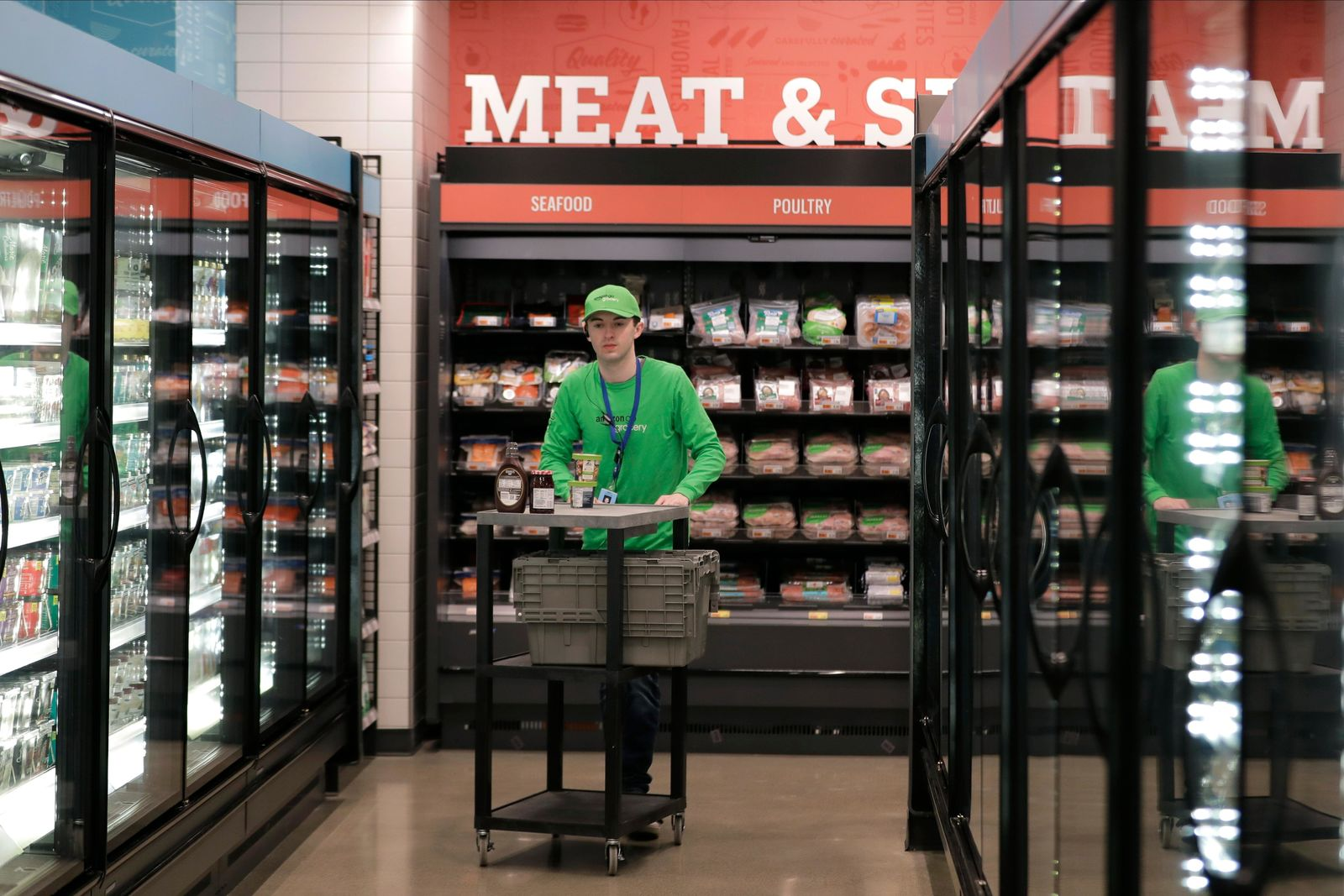 In this Feb. 21, 2020 photo, a worker pushes a cart inside an Amazon Go Grocery store set to open soon in Seattle's Capitol Hill neighborhood. (AP Photo/Ted S. Warren)
