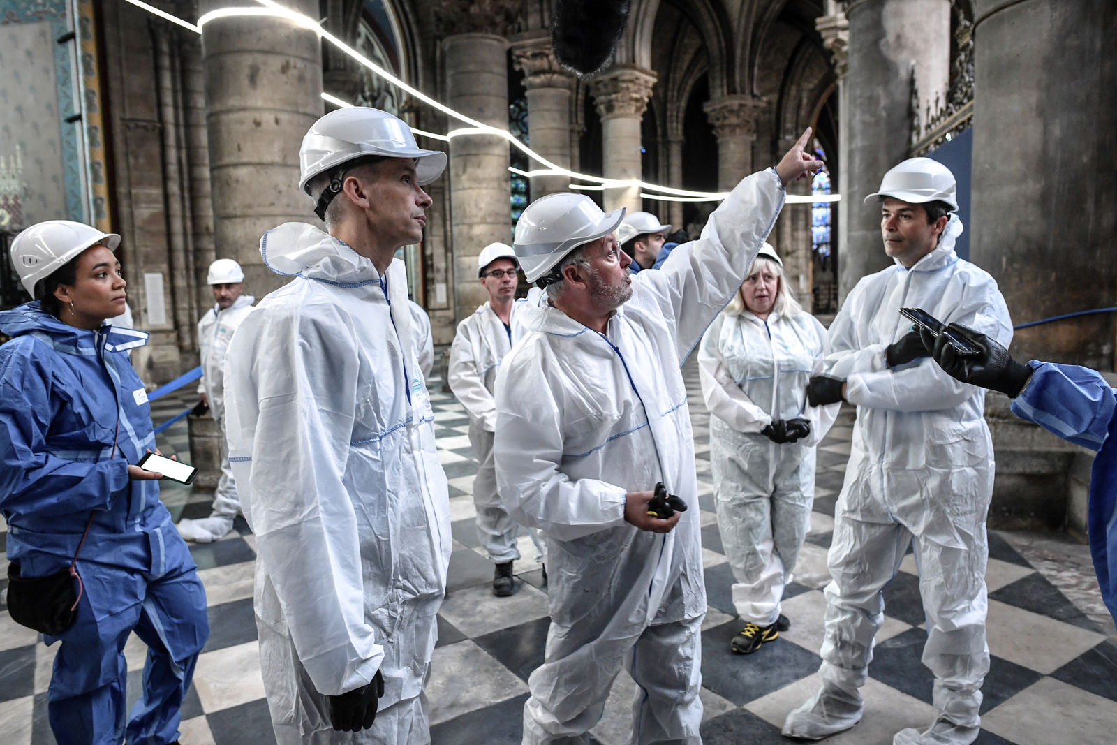 French Culture Minister Franck Riester, second left, listens to French chief architect of historical sites Philippe Villeneuve, center, as they visit the Notre-Dame de Paris Cathedral three months after a major fire Wednesday, July 17, 2019 in Paris. The chief architect of France's historic monuments says that three months after the April 15 fire that devastated Notre Dame Cathedral the site is still being secured. (Stephane de Sakutin/Pool via AP)
