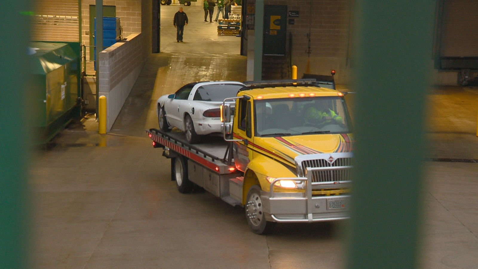 A tow truck hauls away a car that crashed into the loading dock area of Lambeau Field, December 22, 2017. (WLUK)<p></p>