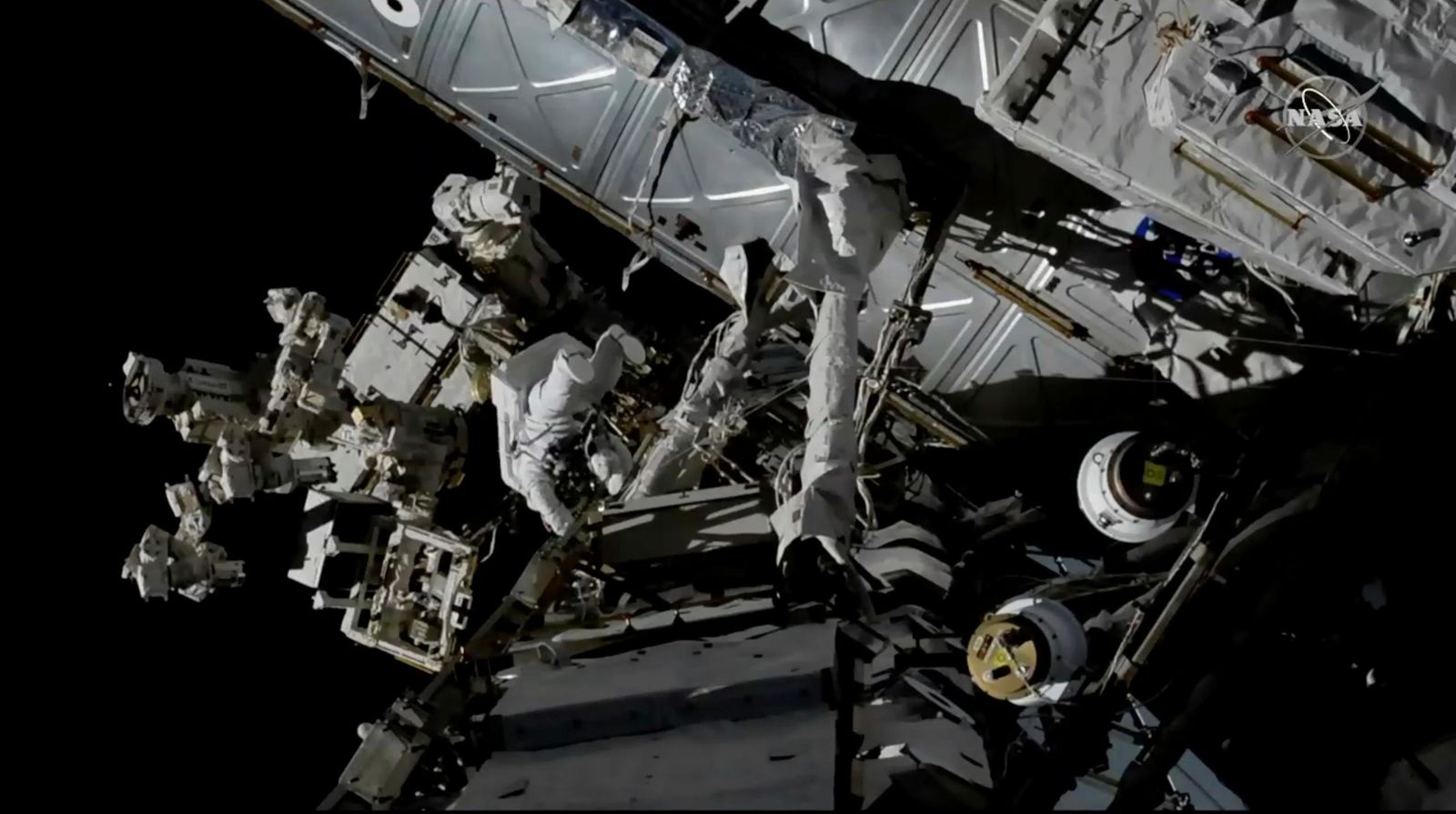 In this photo provided by NASA, Canadian astronaut David Saint-Jacques, center left, works outside the International Space Station, Monday, April 8, 2019. s the third spacewalk in just 2 ½ weeks for the station crew. (NASA via AP)