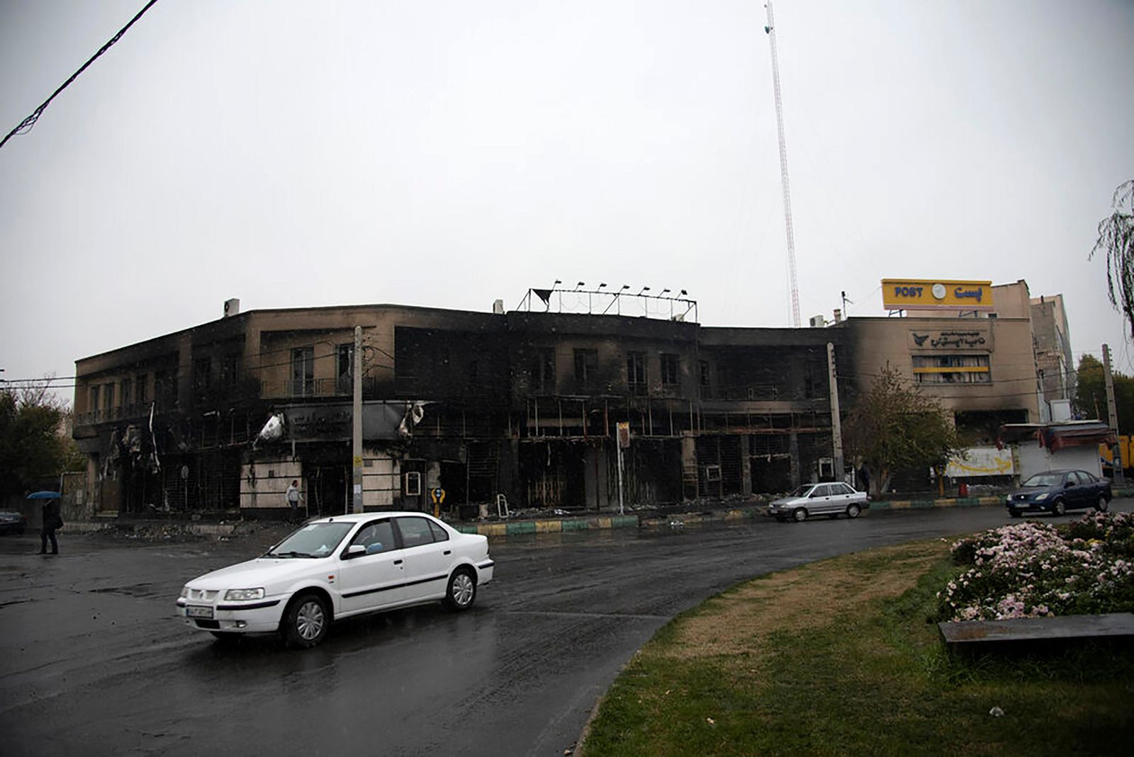 In this photo taken Monday, Nov. 18, 2019, and released by the Iranian Students' News Agency, ISNA, cars drive past a building which burned during protests that followed the authorities' decision to raise gasoline prices, in the city of Karaj, west of the capital Tehran, Iran. (Masoume Aliakbar/ISNA via AP)