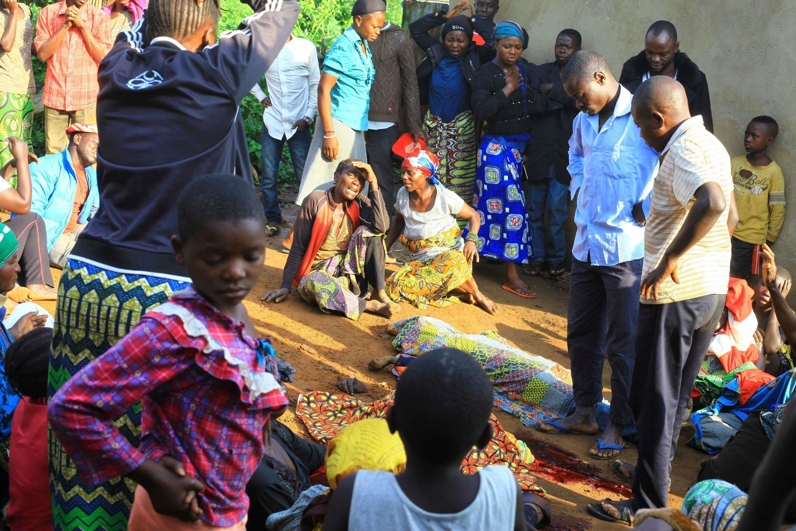 In this photo taken Friday, Oct 5, 2018, family members and onlookers mourn over bodies of civilians killed by The Allied Democratic Forces rebels in Beni, Eastern Congo. (AP Photo/Al-hadji Kudra Maliro)