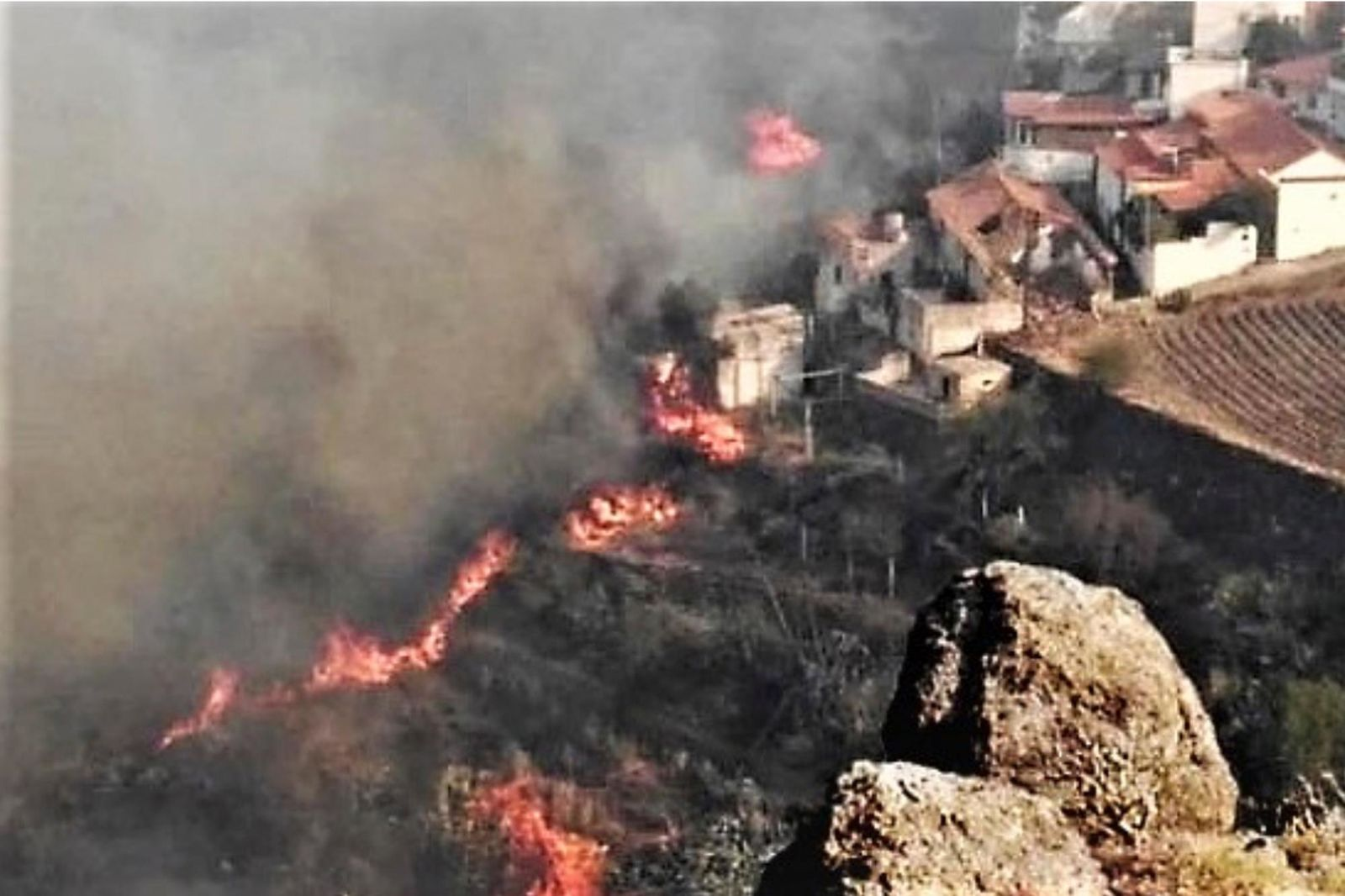 In this photo issued by Cabildo de Gran Canaria, flames from a forest fire burn close to houses in El Rincon, Tejeda on the Spanish Gran Canaria island on Sunday Aug. 18, 2019.(Cabildo de Gran Canaria Via AP)