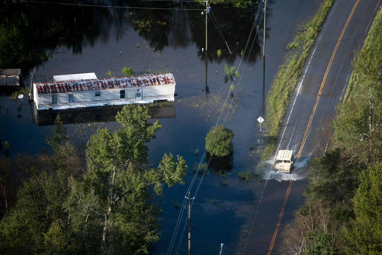 A truck drives through floodwaters after Hurricane Florence struck the Carolinas, Monday, Sept. 17, 2018, near Conway, S.C. (AP Photo/Sean Rayford)