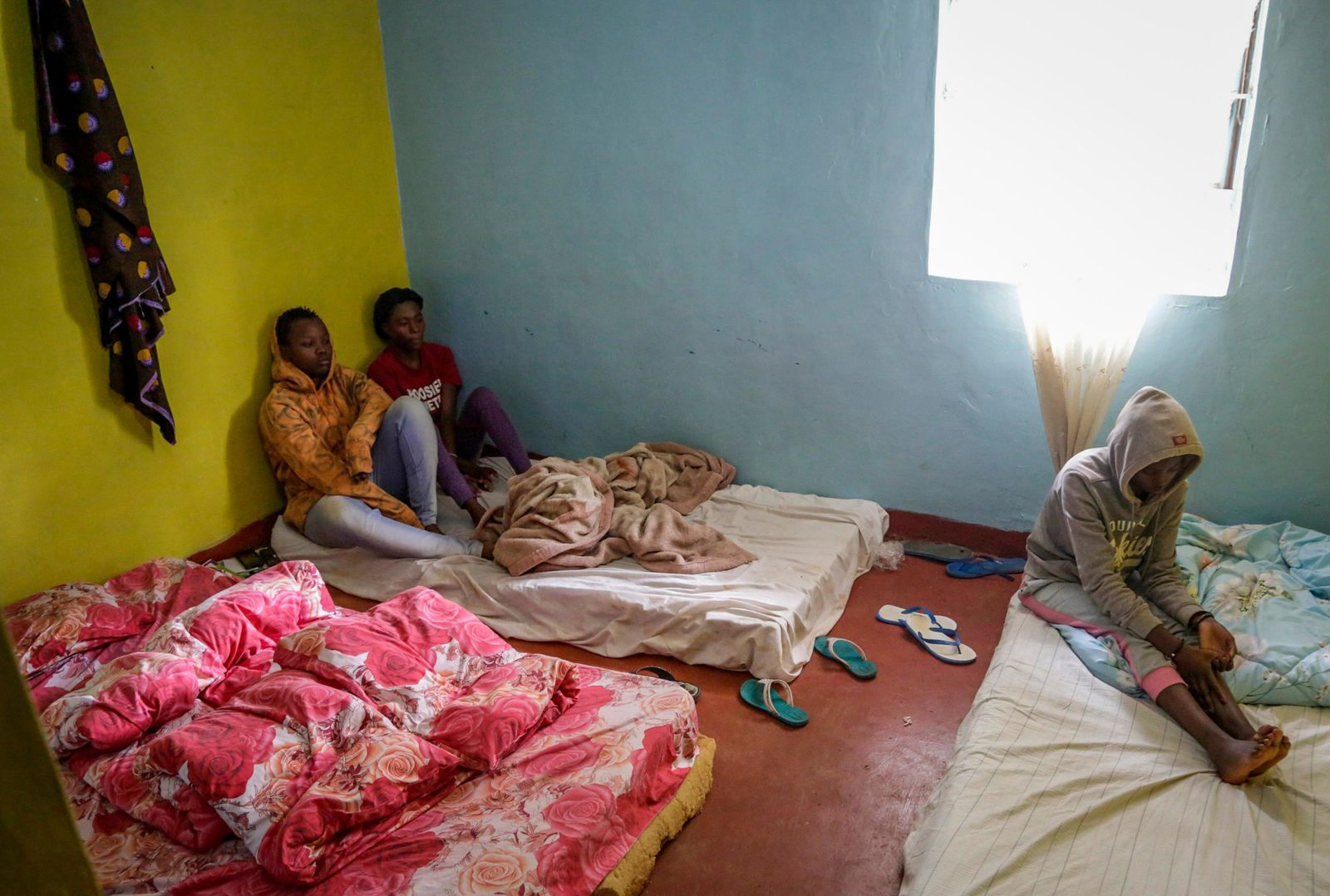 In this photo taken Tuesday, May 28, 2019, LGBT refugee Nina Muregwa, 17, left, from Burundi, who says she left Burundi after her lover's mother threatened to kill her, sits with others in the house where they take shelter in a low-income neighborhood of the capital Nairobi, Kenya(AP Photo/Khalil Senosi)