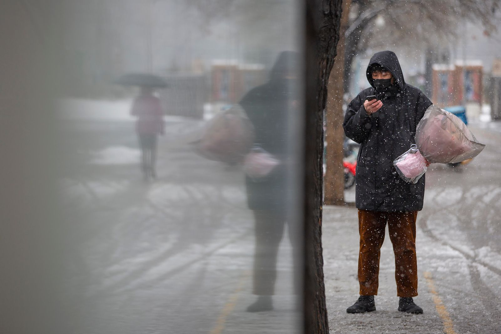 A man wearing a face mask holds a flower bouquet as he stands along a street in Beijing, Friday, Feb. 14, 2020. China on Friday reported another sharp rise in the number of people infected with a new virus, as the death toll neared 1,400. (AP Photo/Mark Schiefelbein)