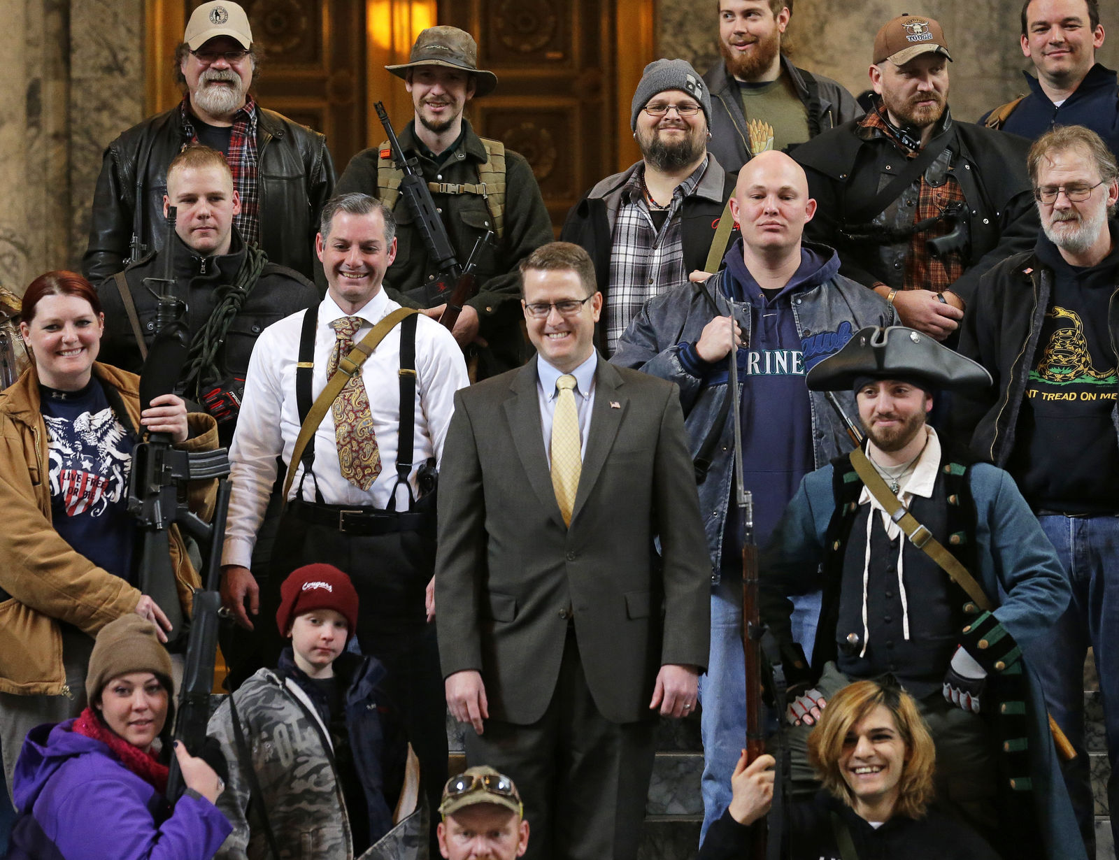 FILE - In this Jan. 15, 2015, file photo, Washington Rep. Matt Shea, R-Spokane Valley, center, poses for a group photo with gun owners inside the Capitol in Olympia, Wash., following a gun-rights rally.{ } (AP Photo/Ted S. Warren, File)