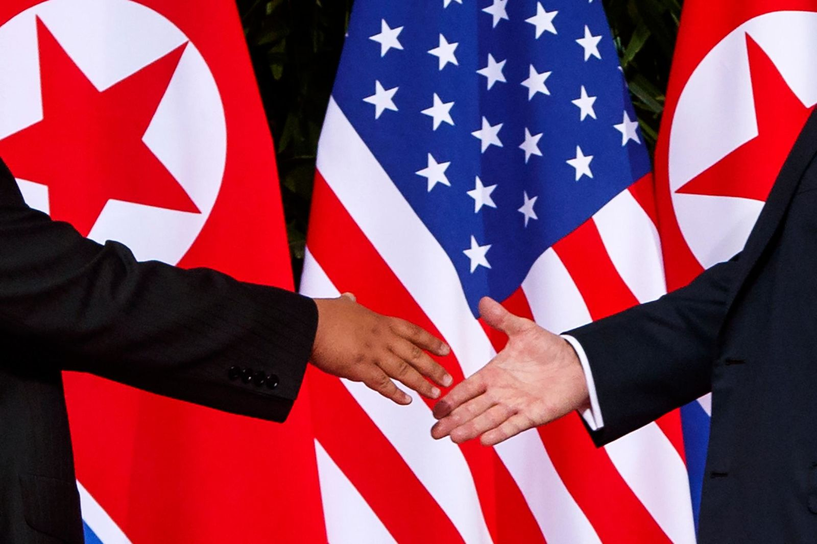 FILE - In this Tuesday, June 12, 2018, file photo, U.S. President Donald Trump, right, reaches to shake hands with North Korea leader Kim Jong Un at the Capella resort on Sentosa Island in Singapore. (AP Photo/Evan Vucci, File)