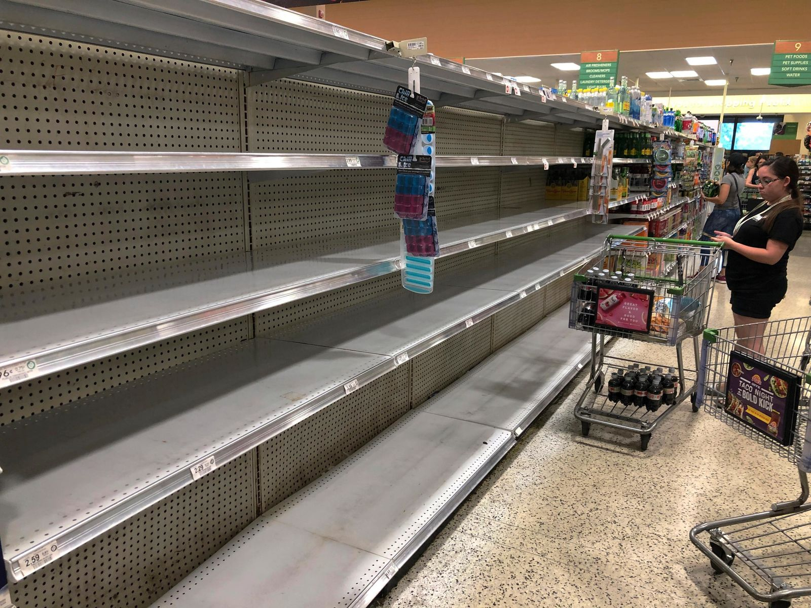 Store shelves are empty of bottled water as residents buy supplies in preparation for Hurricane Dorian,  in Doral, Fla., Thursday, July 29, 2019.{ } (AP Photo/Marcus Lim)