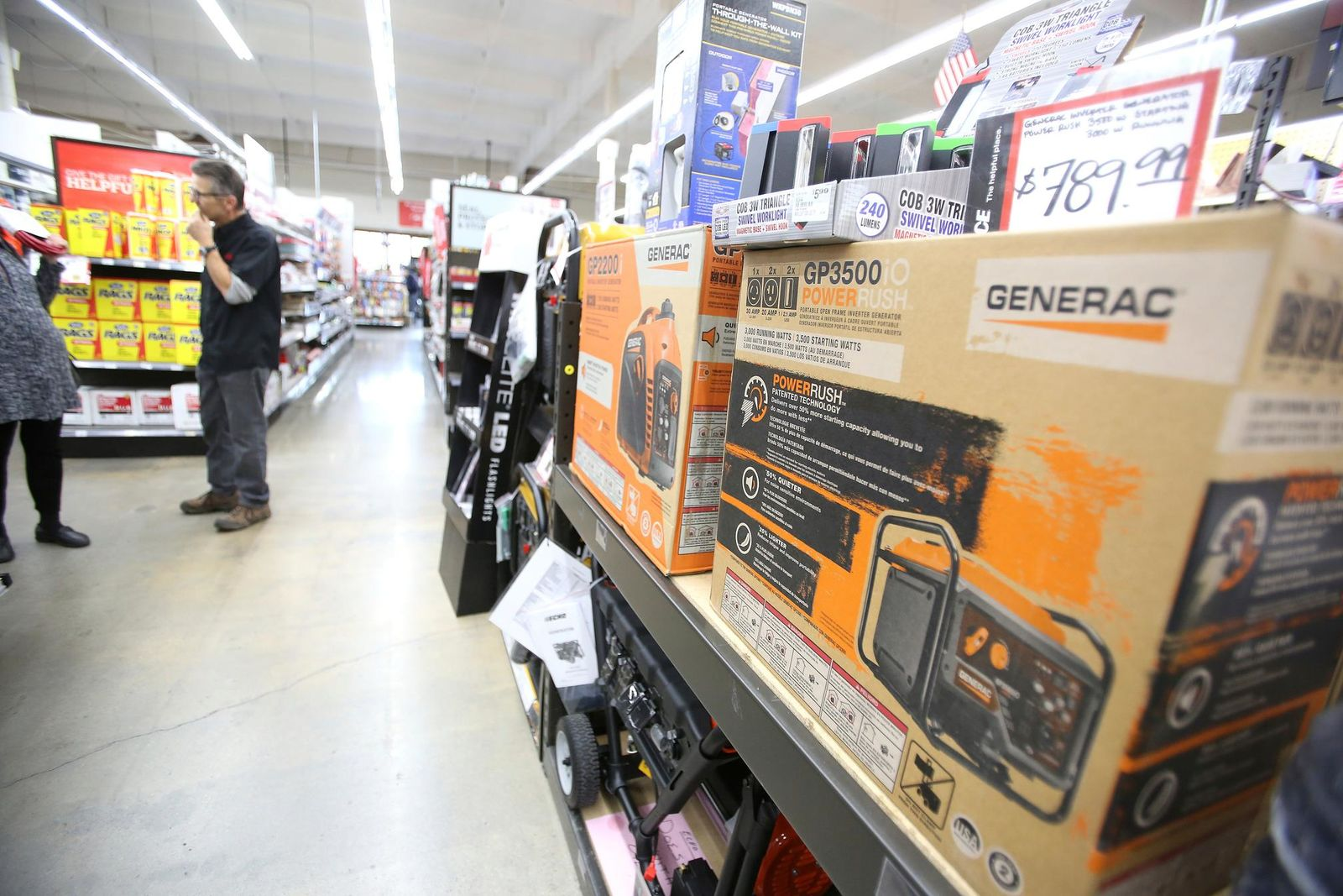 A shelf of Generac generators sit on the shelf while potential customers ask questions about them Tuesday afternoon at B&C Ace Home & Garden hardware store in Grass Valley's Glenbrook Basin. (Elias Funez/The Union via AP)