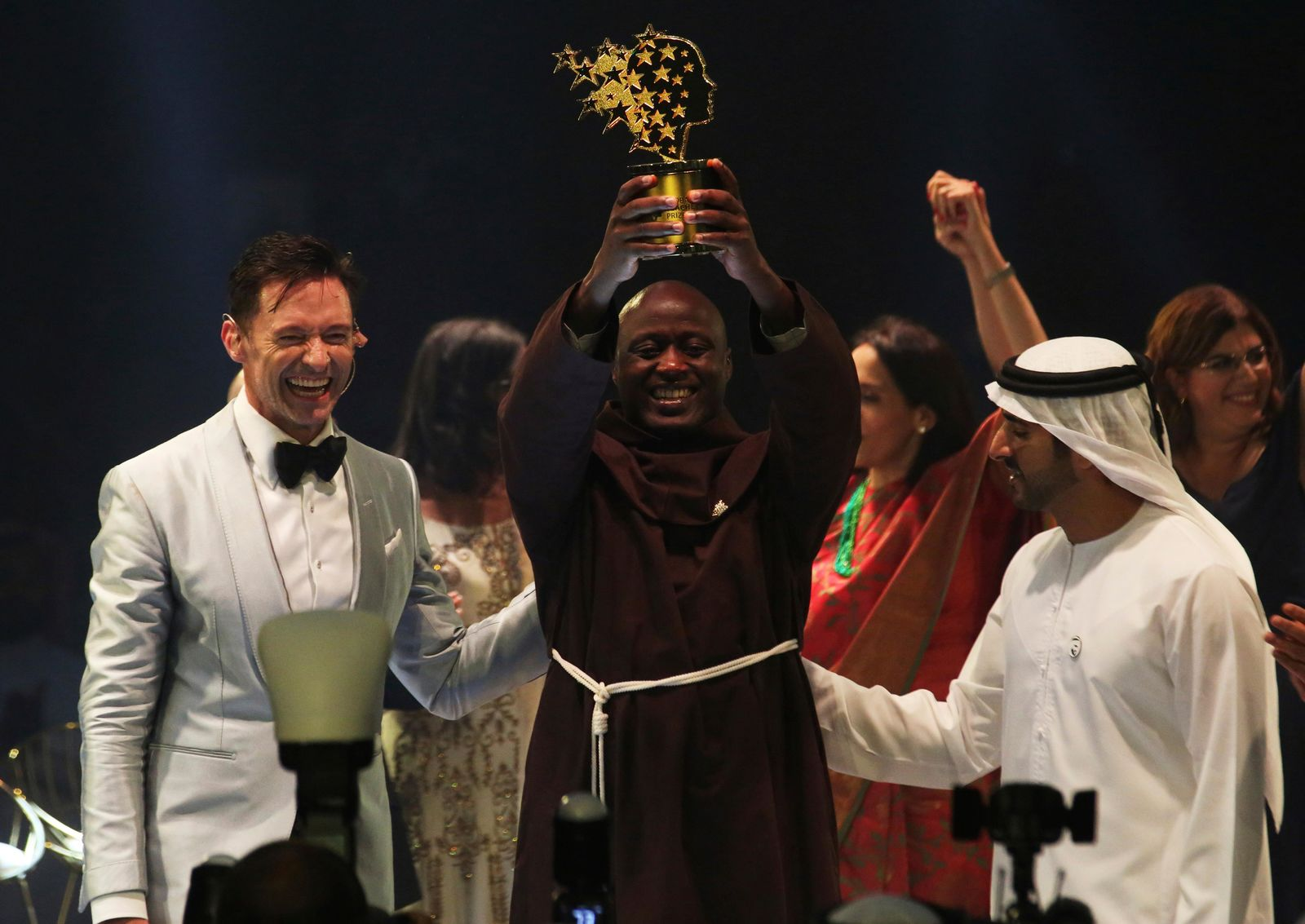 Kenyan teacher Peter Tabichi, center, actor Hugh Jackman, left, and Dubai crown prince Sheikh Hamdan bin Mohammed Al Maktoum, right, react after Tabichi won the $1 million Global Teacher Prize in Dubai, United Arab Emirates, Sunday, March 24, 2019(AP Photo/Jon Gambrell)