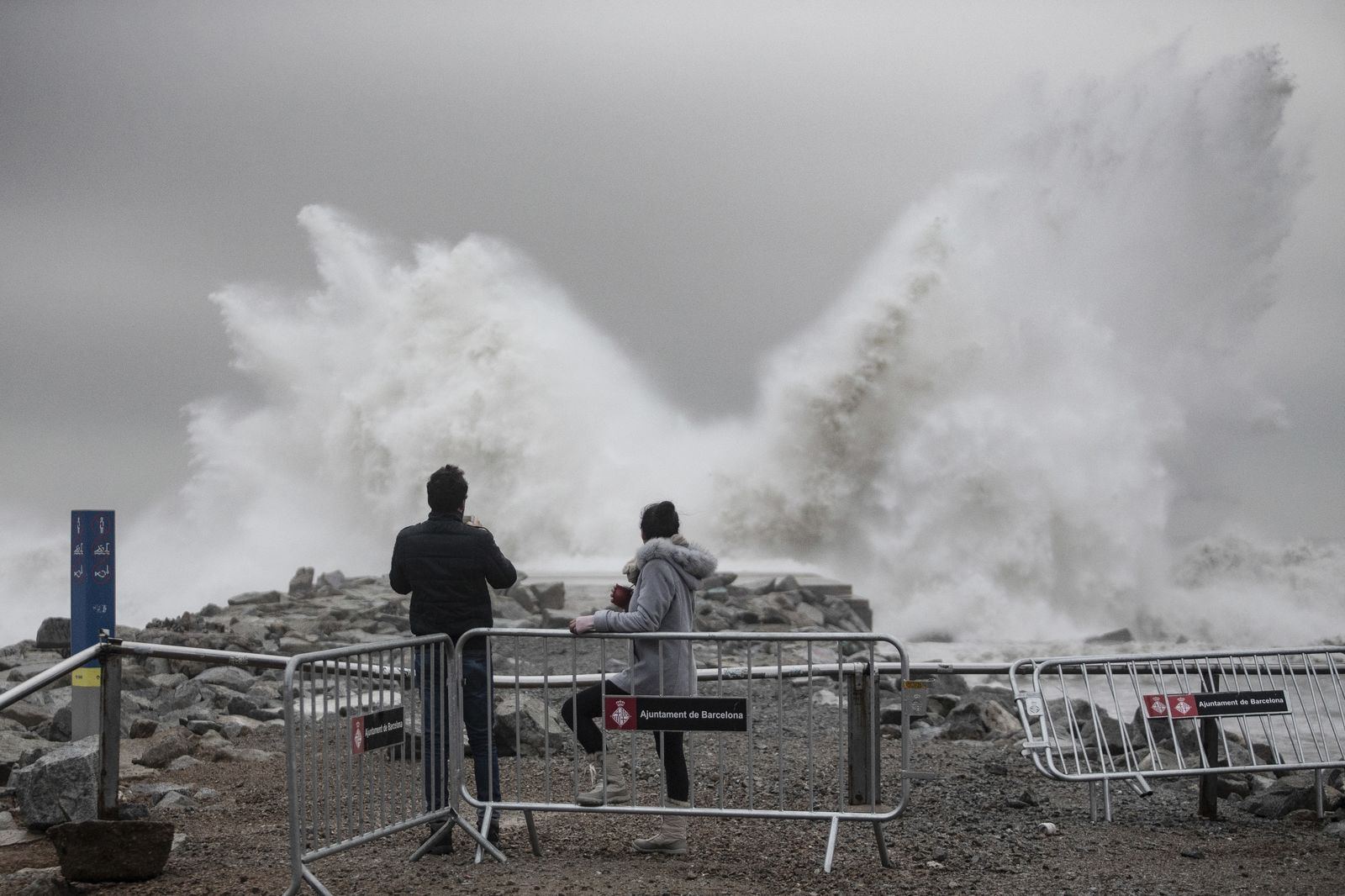 Two people watch the waves hitting the breakwater in Barcelona, Spain, Wednesday, Jan. 22, 2020.{ } (AP Photo/Joan Mateu)