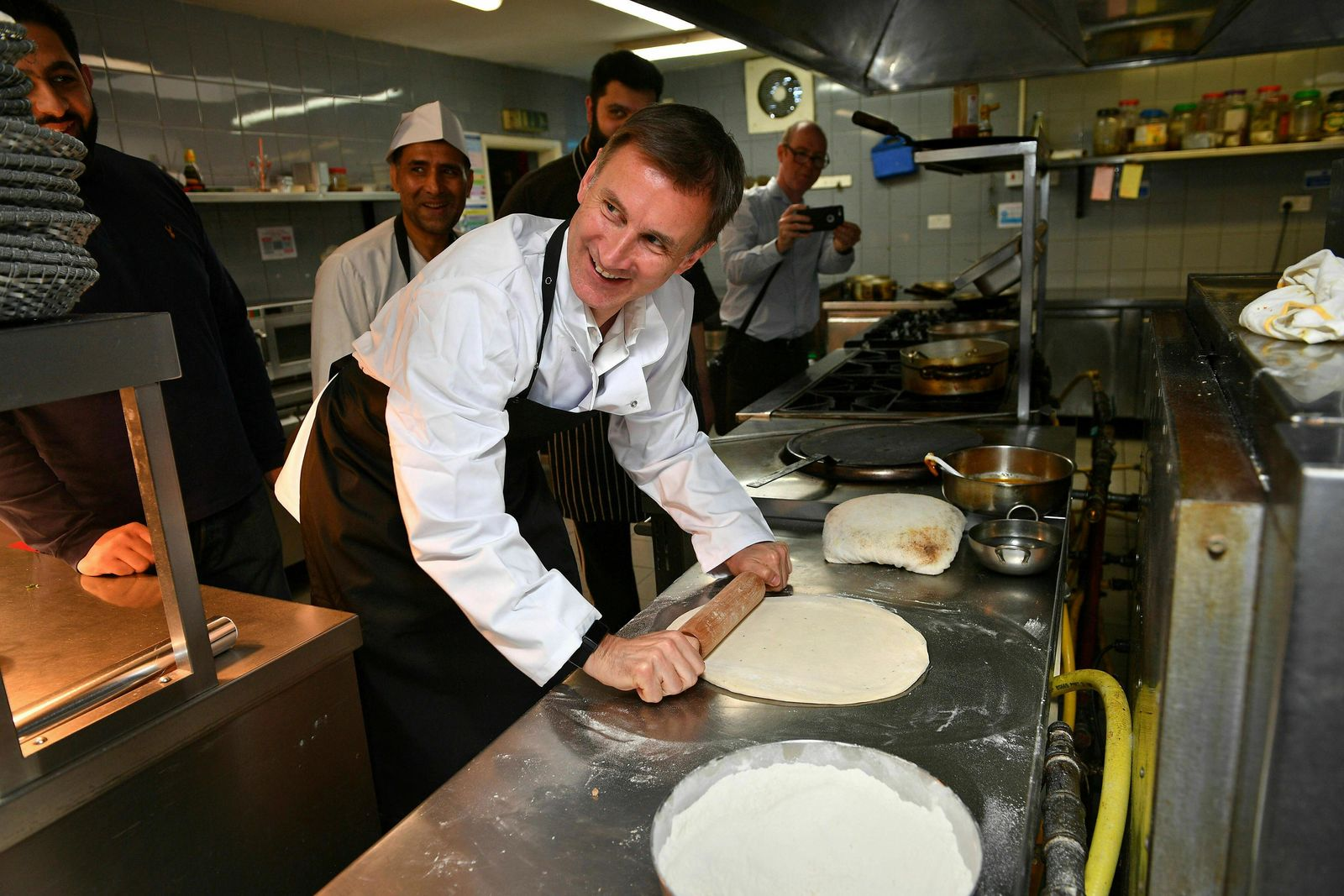 Conservative Party leadership candidate Jeremy Hunt rolls a naan bread as he visits Imran's Balti Restaurant ahead of the first Tory party hustings, in Birmingham, England, Saturday June 22, 2019. (Ben Birchall/PA via AP)