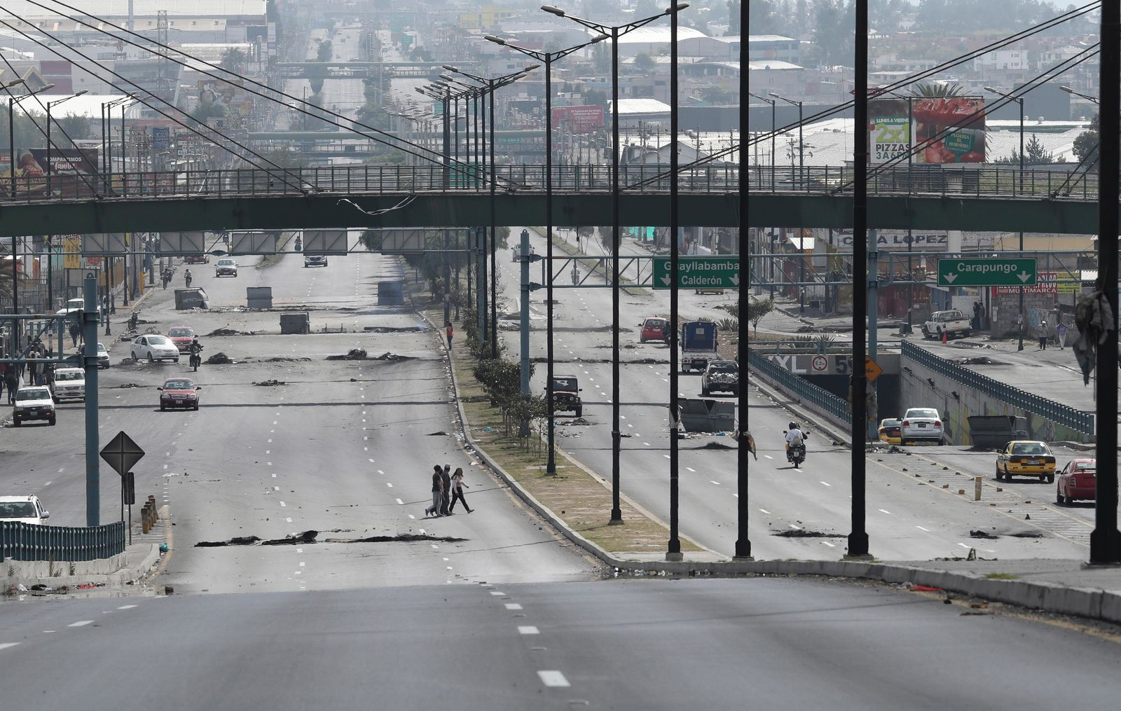 Few commuters make their way across the Pan American Highway, full of roadblocks placed by anti-government protesters, during a 24-hour military curfew and a day after violent protests across Quito, Ecuador, Sunday, Oct. 13, 2019. (AP Photo/Dolores Ochoa)