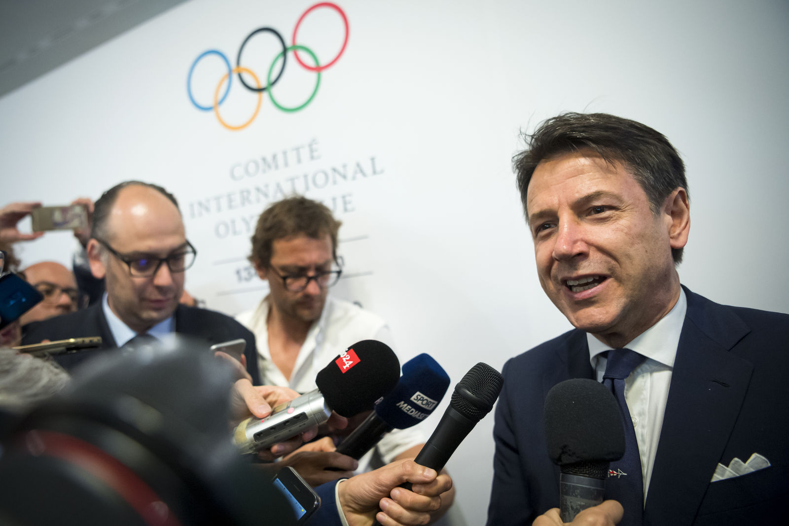 Italian Prime minister Giuseppe Conte speaks to journalists as he arrives during the first day of the 134th Session of the International Olympic Committee (IOC), at the SwissTech Convention Centre, in Lausanne, Switzerland, Monday, June 24, 2019.{ } (Jean-Christophe Bott/Keystone via AP)