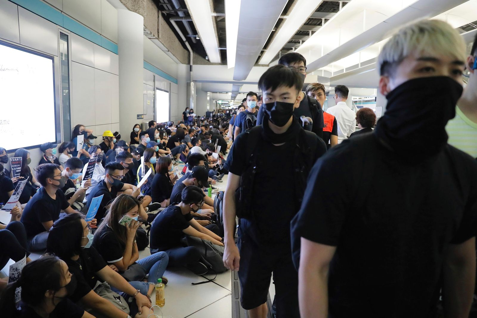 "Demonstrators sit during a protest at the Yuen Long MTR station, where demonstrators and others were violently attacked by men in white T-shirts following an earlier protest in July, in Hong Kong, Wednesday, Aug. 21, 2019. Japan's top diplomat on Tuesday told his Chinese counterpart that Japan is ""deeply concerned"" about the continuing protests in Hong Kong. (AP Photo/Kin Cheung)"