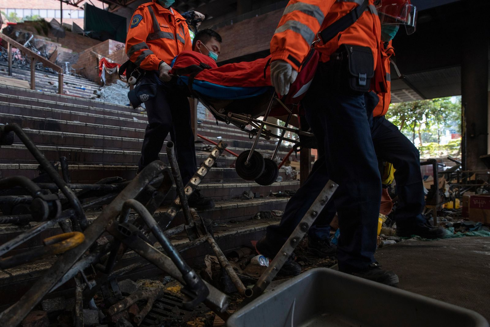 A man is evacuated by medics past charred debris from the Polytechnic University in Hong Kong on Wednesday, Nov. 20, 2019. (AP Photo/Ng Han Guan)