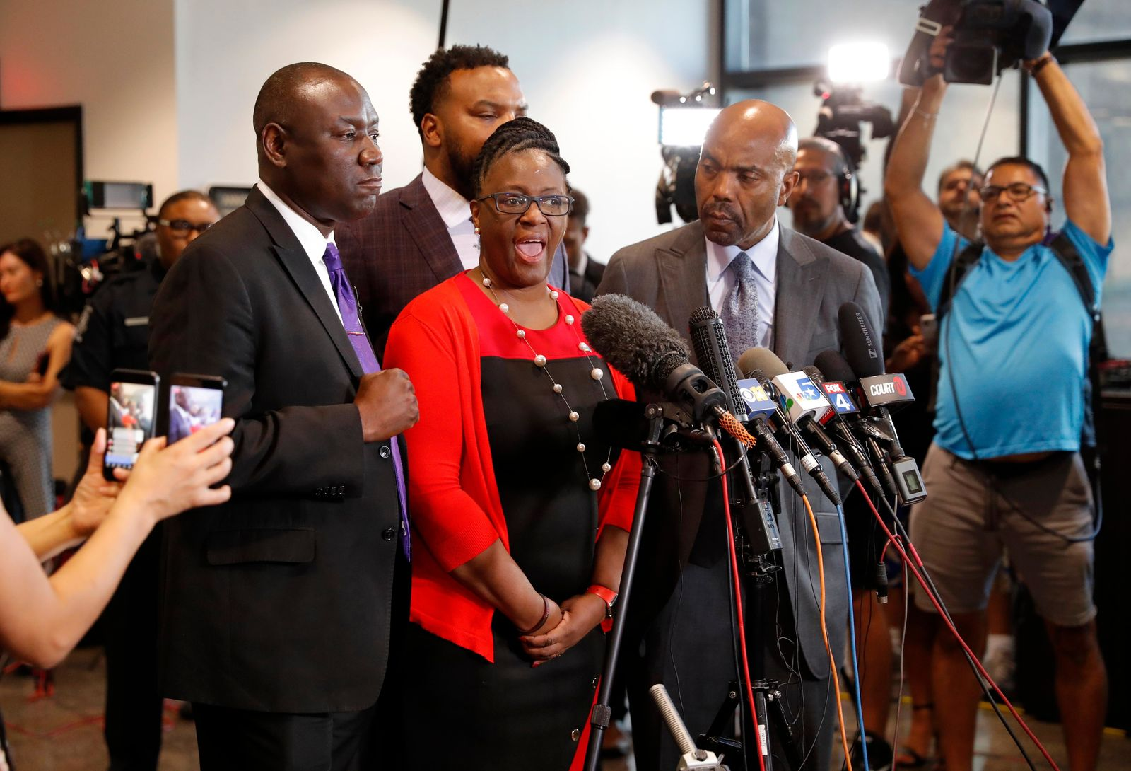 Allison Jean, center, mother of Botham Jean, makes comments during a news conference as attorneys Ben Crump, left, Lee Merritt, rear, and Daryl Washington, right, look on after the sentencing phase of former Dallas police officer Amber Guyger murder trial at Frank Crowley Court Building in Dallas, Wednesday, Oct. 2, 2019. (AP Photo/Tony Gutierrez)