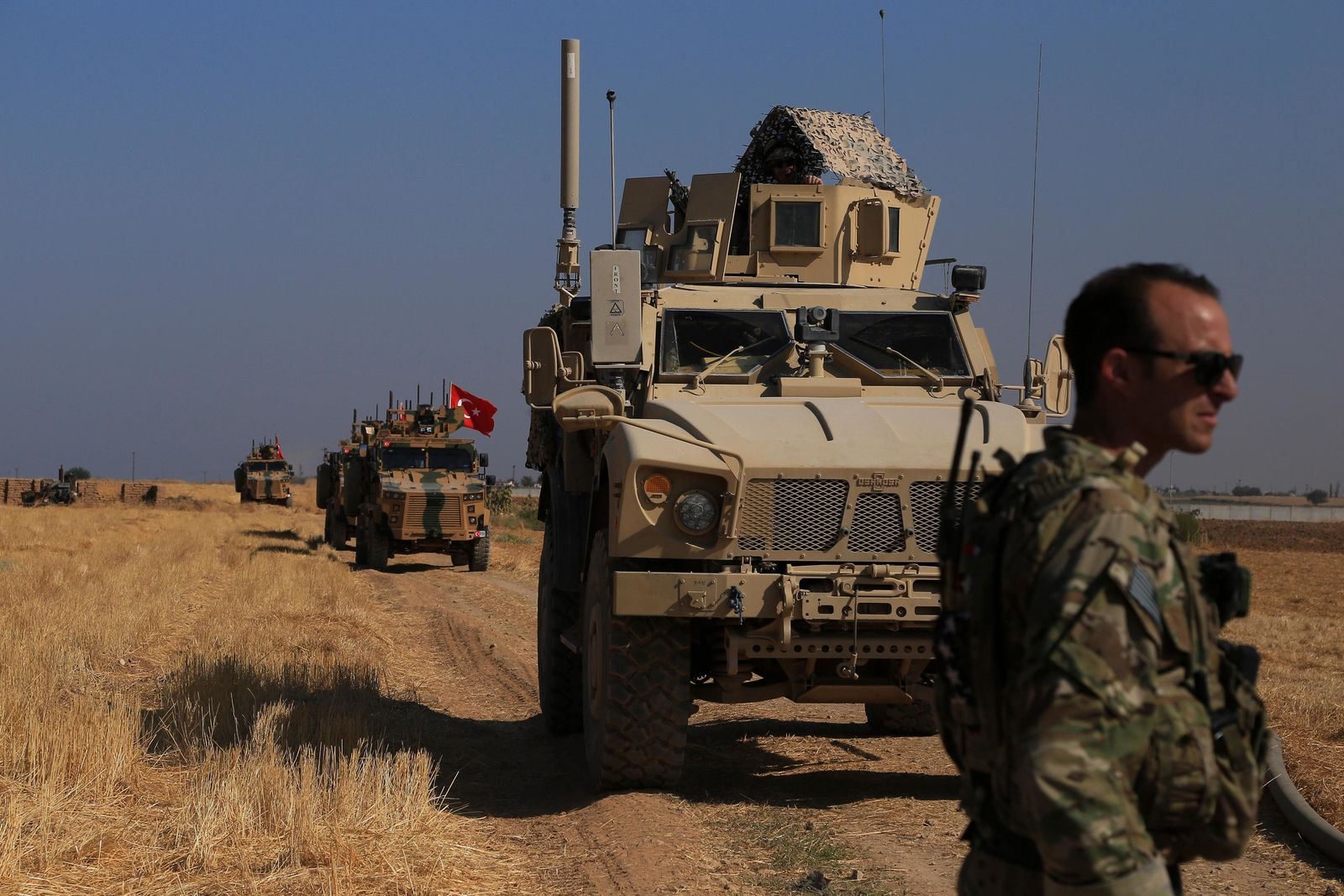 "Turkish and American armored vehicles patrol as they conduct joint ground patrol in the so-called ""safe zone"" on the Syrian side of the border with Turkey, near the town of Tal Abyad, northeastern Syria, Friday, Oct.4, 2019. The patrols are part of a deal reached between Turkey and the United States to ease tensions between the allies over the presence of U.S.-backed Syrian Kurdish fighters in the area. (AP Photo/Baderkhan Ahmad)"