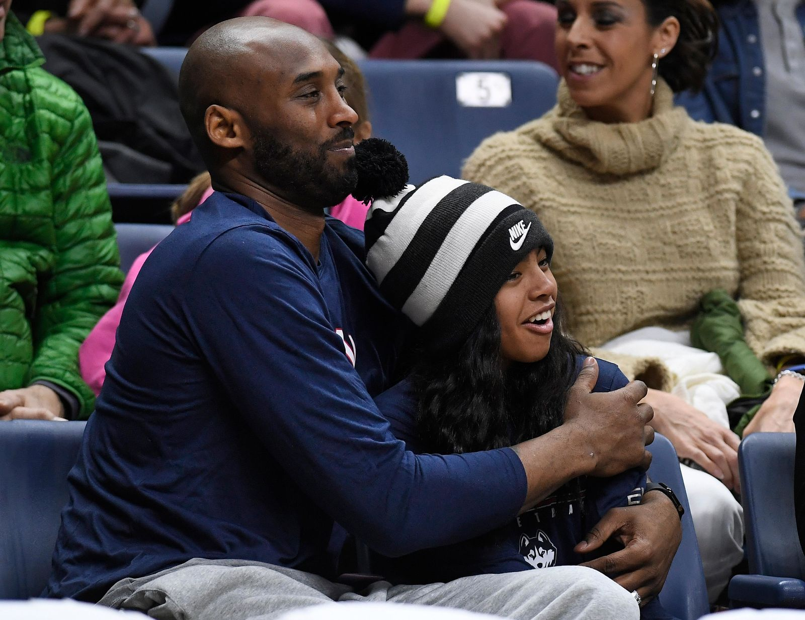 FILE - In this March 2, 2019, file photo Kobe Bryant and his daughter Gianna watch the first half of an NCAA college basketball game between Connecticut and Houston in Storrs, Conn.{ } (AP Photo/Jessica Hill, File)