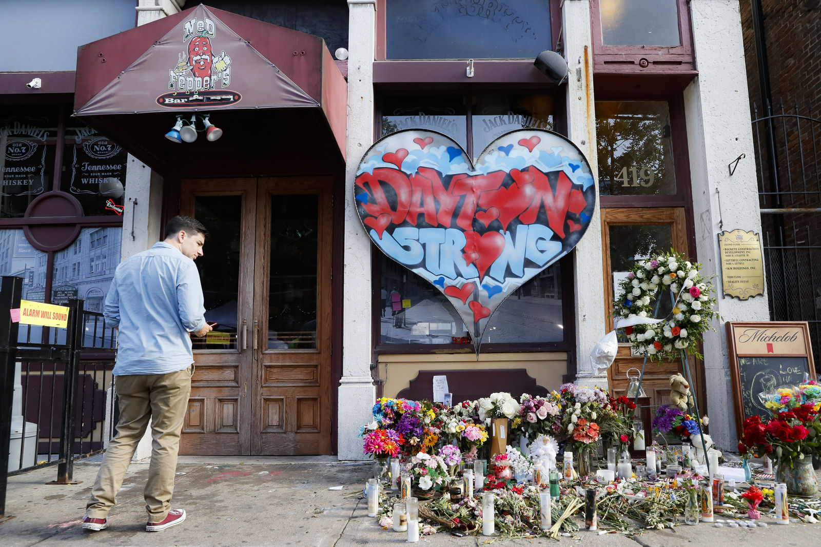 A pedestrian passes a makeshift memorial for the slain and injured victims of a mass shooting that occurred in the Oregon District early Sunday morning, Wednesday, Aug. 7, 2019, in Dayton, Ohio. (AP Photo/John Minchillo)