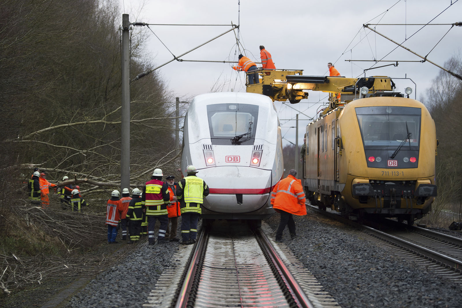 An ICE train of the Deutsche Bahn, left, is stopped on the track between Hannover and Goettingen near the village of Lamspringe, Germany, Thursday, Jan. 18, 2017, as rail workers on a maintenance train repair overhead power wires whilst others clear debris caused by fallen trees.(Swen Pf'rtner/dpa via AP)