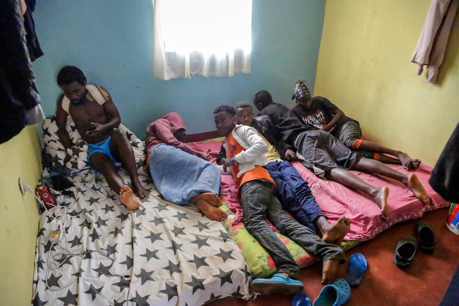 In this photo taken Tuesday, May 28, 2019, LGBT refugees from Burundi, Rwanda and Congo lie on a mattress in one of the rooms they share in the house where they take shelter in a low-income neighborhood of the capital Nairobi, Kenya.{ } (AP Photo/Khalil Senosi)