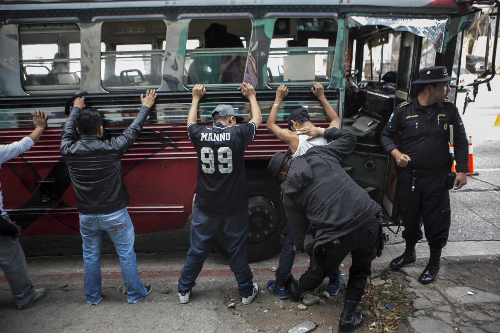 Police search passengers after stopping a bus in the El Milagro area of the Mixco municipality on the outskirts of Guatemala City, Friday, Jan. 17, 2020.{ } (AP Photo/Oliver de Ros)