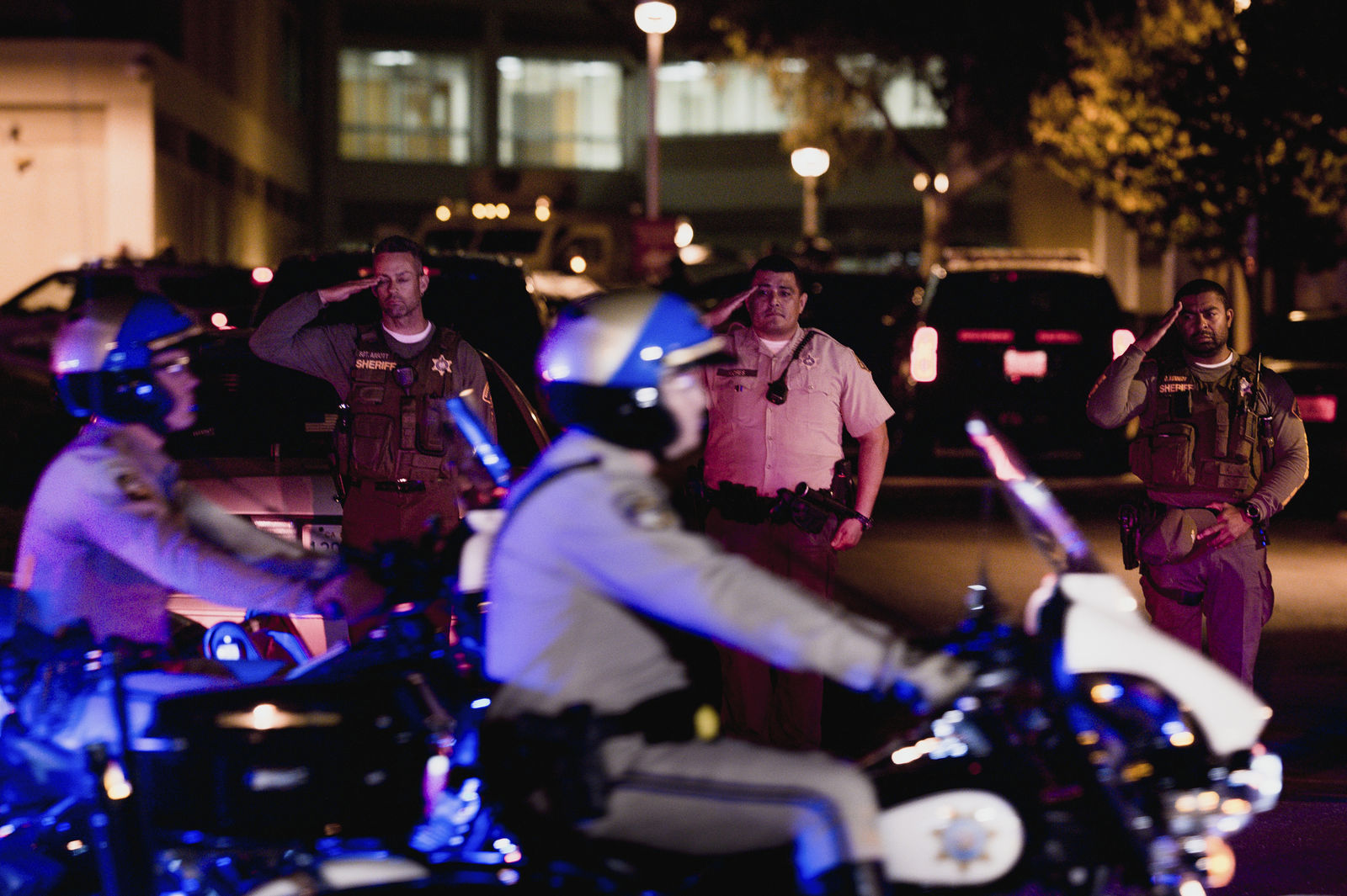 Sheriff deputies salute as California Highway Patrol motorcycle officers lead the procession for a fallen California Highway Patrol officer at Riverside University Health System Medical Center in Moreno Valley, Calif., on Monday, Aug 12, 2019. Moye was killed during a shootout following a traffic stop