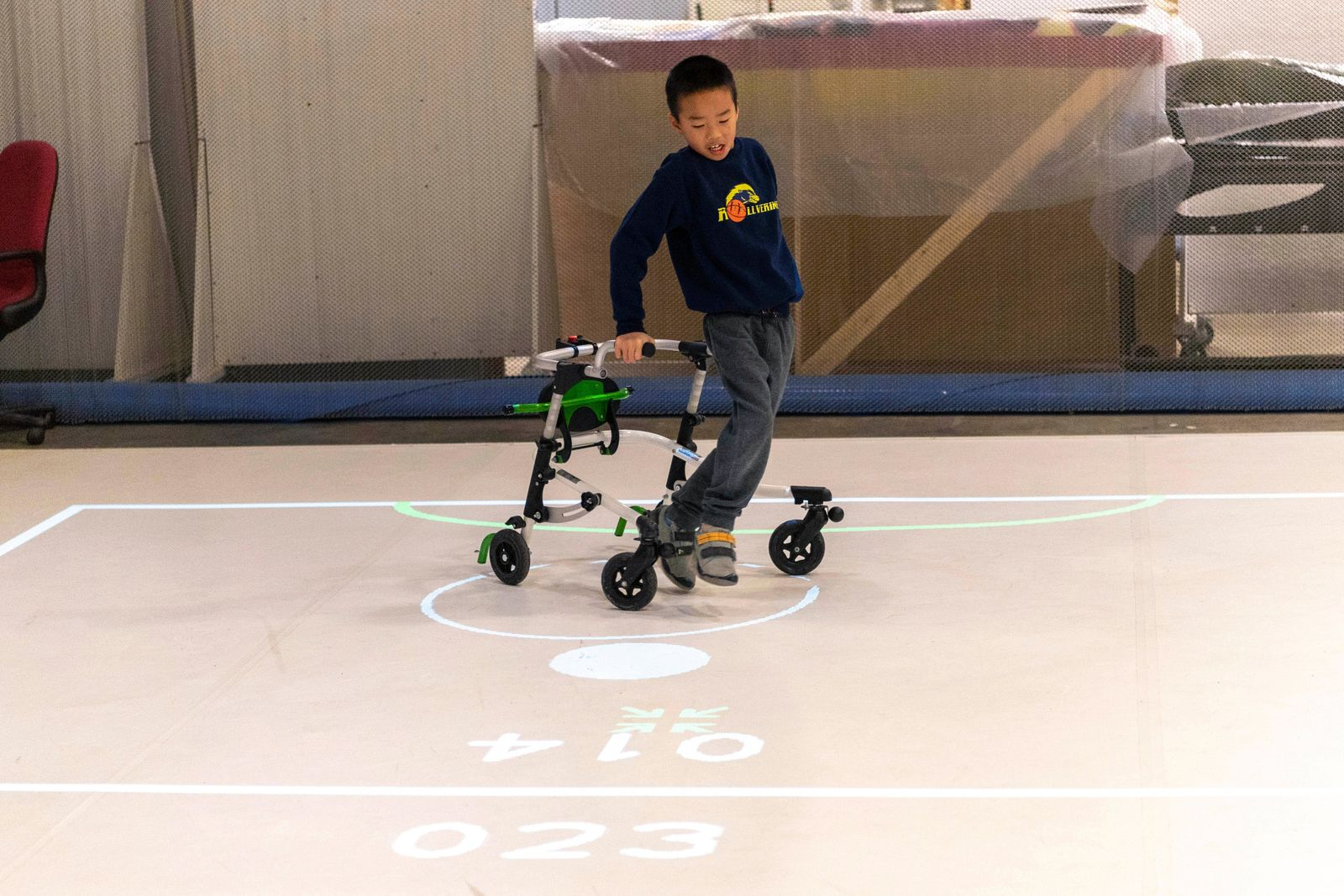 In this Nov. 17, 2019, photo provided by the University of Michigan, Bryan Kreps plays a game modeled after soccer and air hockey using the iGYM system at the university in Ann Arbor, Mich. A University of Michigan research team has created iGYM, an augmented reality system that allows people with different levels of mobility to play and exercise together. (Roger Hart/University of Michigan via AP)
