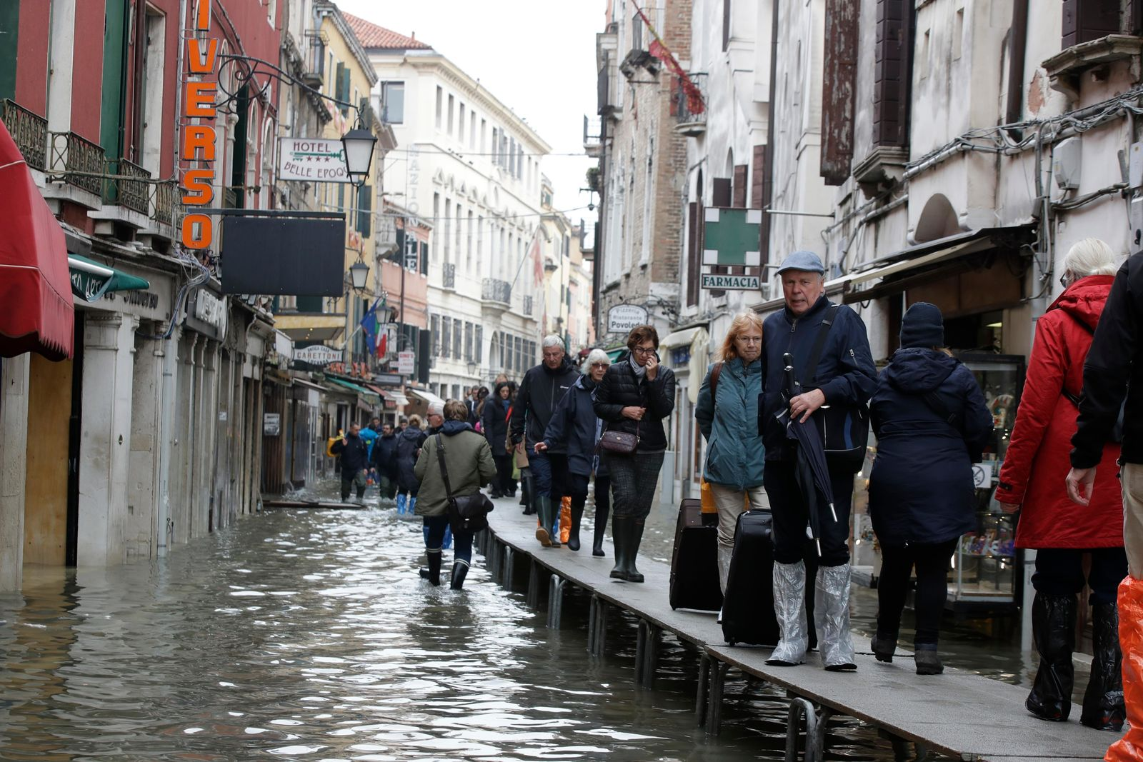 Tourist pull their suitcases along catwalks set up during a high tide, in Venice, Wednesday, Nov. 13, 2019.{ } (AP Photo/Luca Bruno)