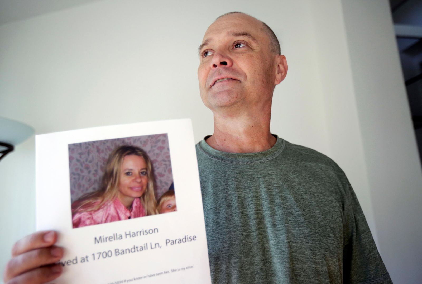 In this Nov. 27, 2018, photo, Bill Engfelt poses for a portrait holding the flyer he made while searching for information on his sister, Mirella Harrison, in Solana Beach, Calif. After a lengthy search, she was found safe. (AP Photo/Gregory Bull)