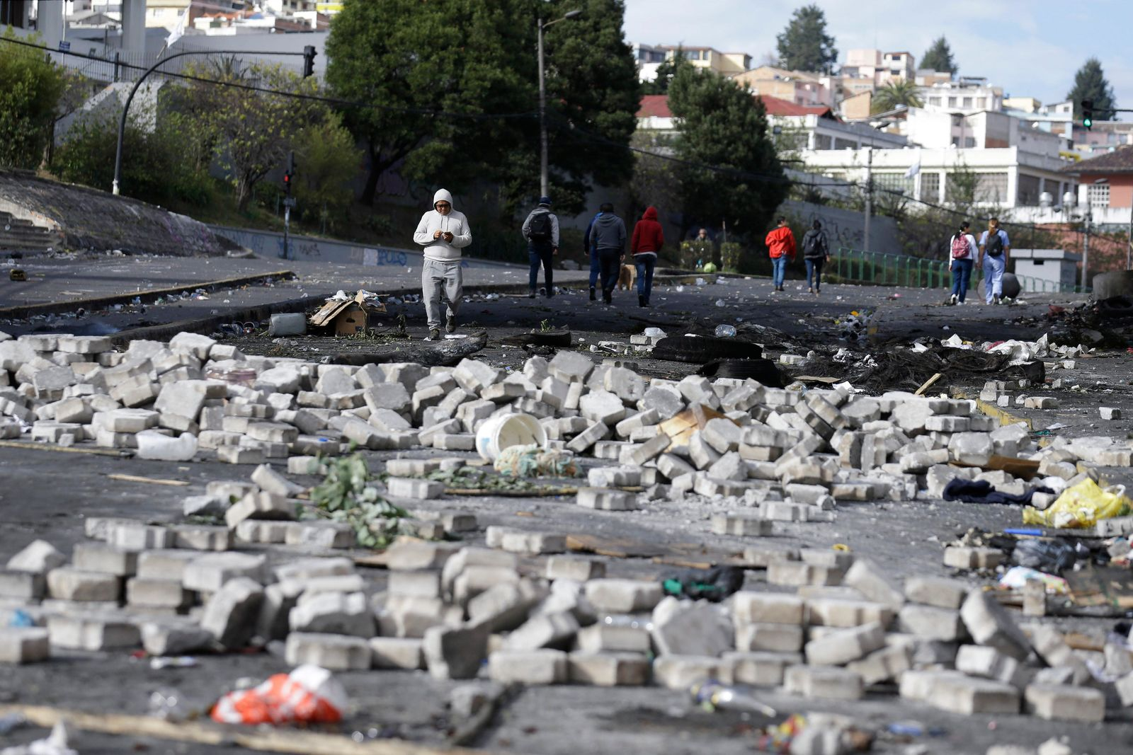 Pedestrians walk through the debris of barricades set by anti-government demonstrators the day after violent protests in Quito, Ecuador, Sunday, Oct. 13, 2019. (AP Photo/Fernando Vergara)