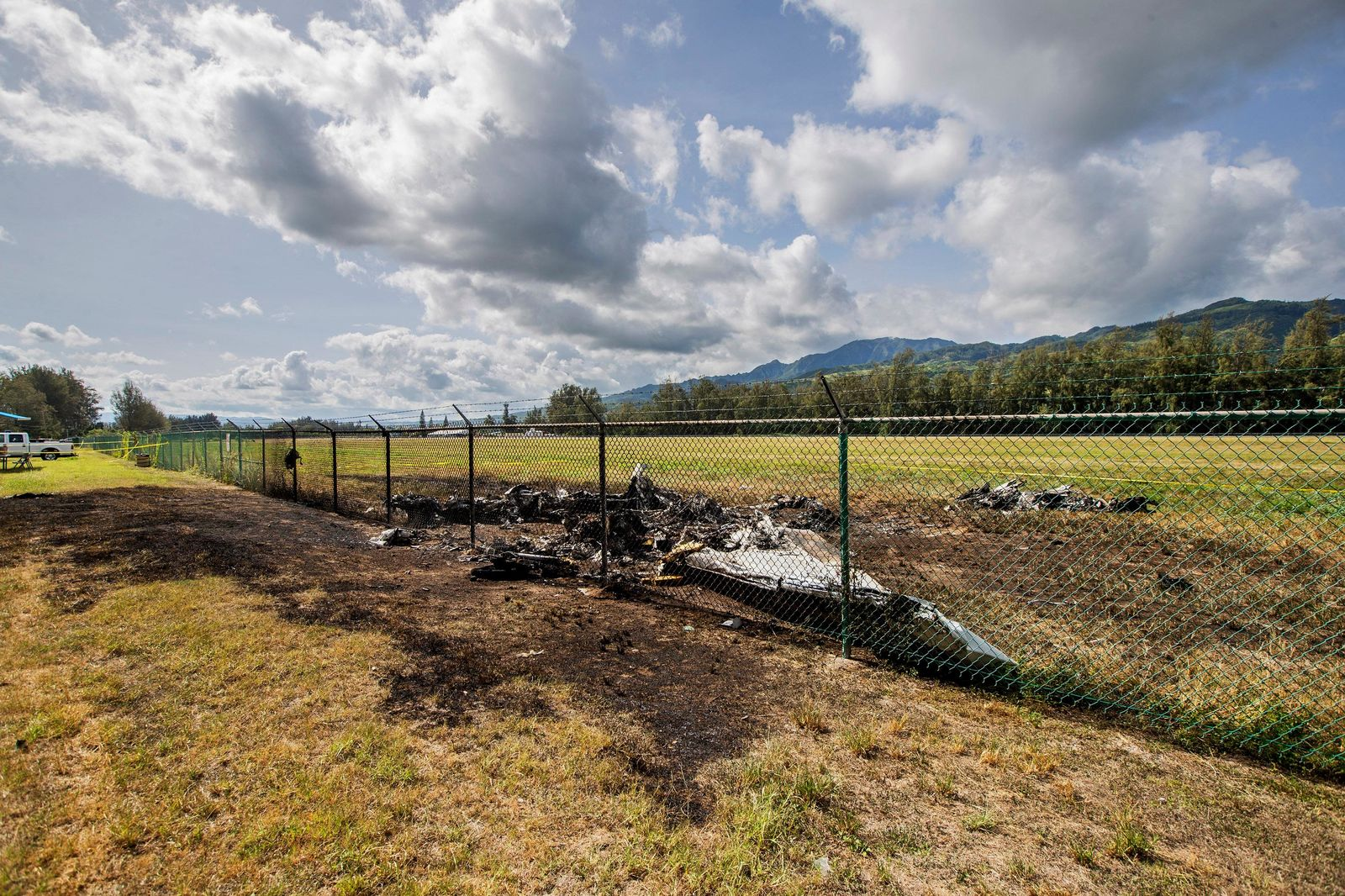 This is the site where a Beechcraft King Air twin-engine plane crashed Friday evening killing multiple people seen on Saturday, June 22, 2019, in Mokuleia, Hawaii. No one aboard survived the skydiving plane crash, which left a small pile of smoky wreckage near the chain link fence surrounding Dillingham Airfield, a one-runway seaside airfield. (Dennis Oda/Honolulu Star-Advertiser via AP)