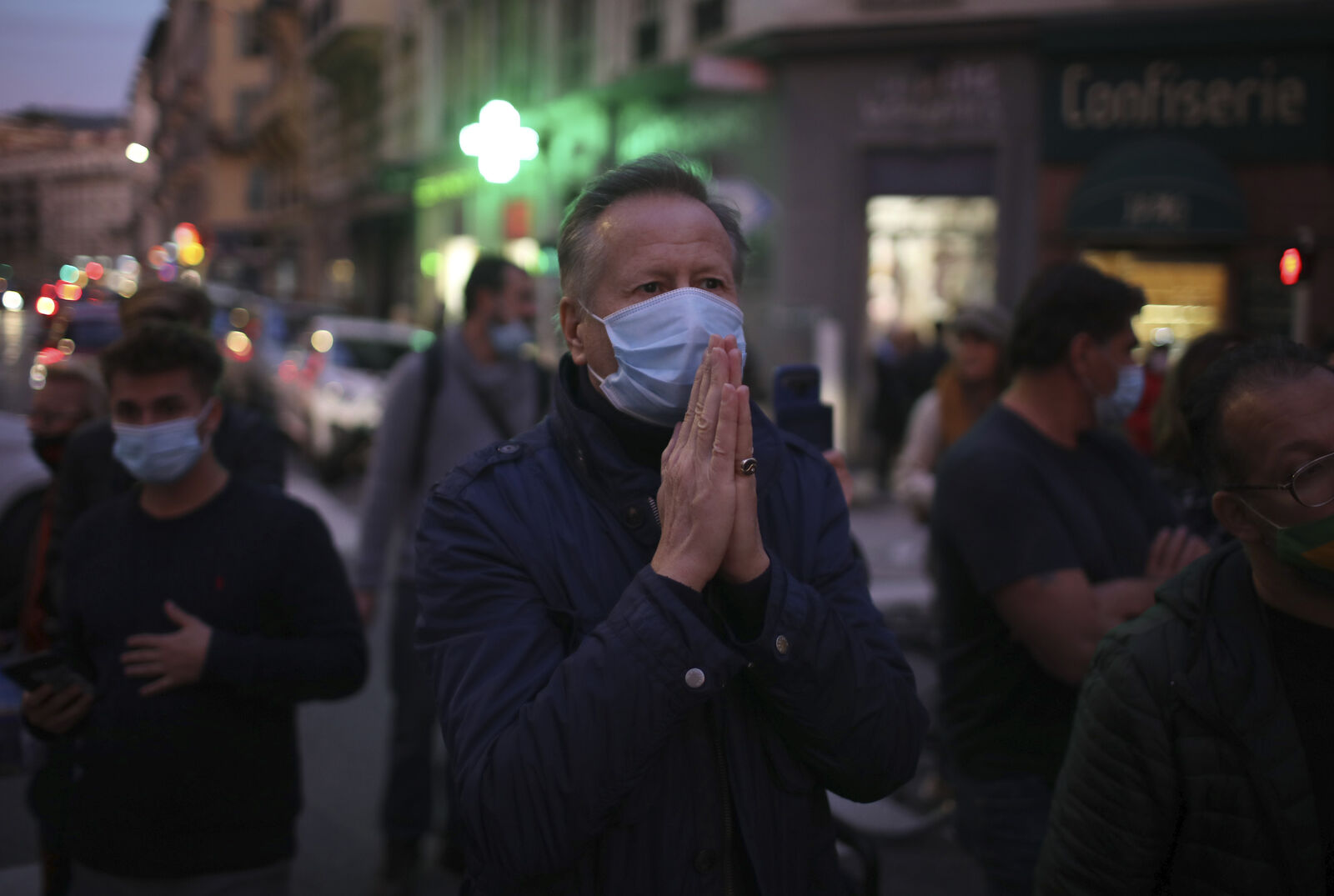 FILE- A man prays in the street outside the Notre Dame church in Nice, southern France, after a knife attack took place on Thursday, Oct. 29, 2020. (AP Photo/Daniel Cole)
