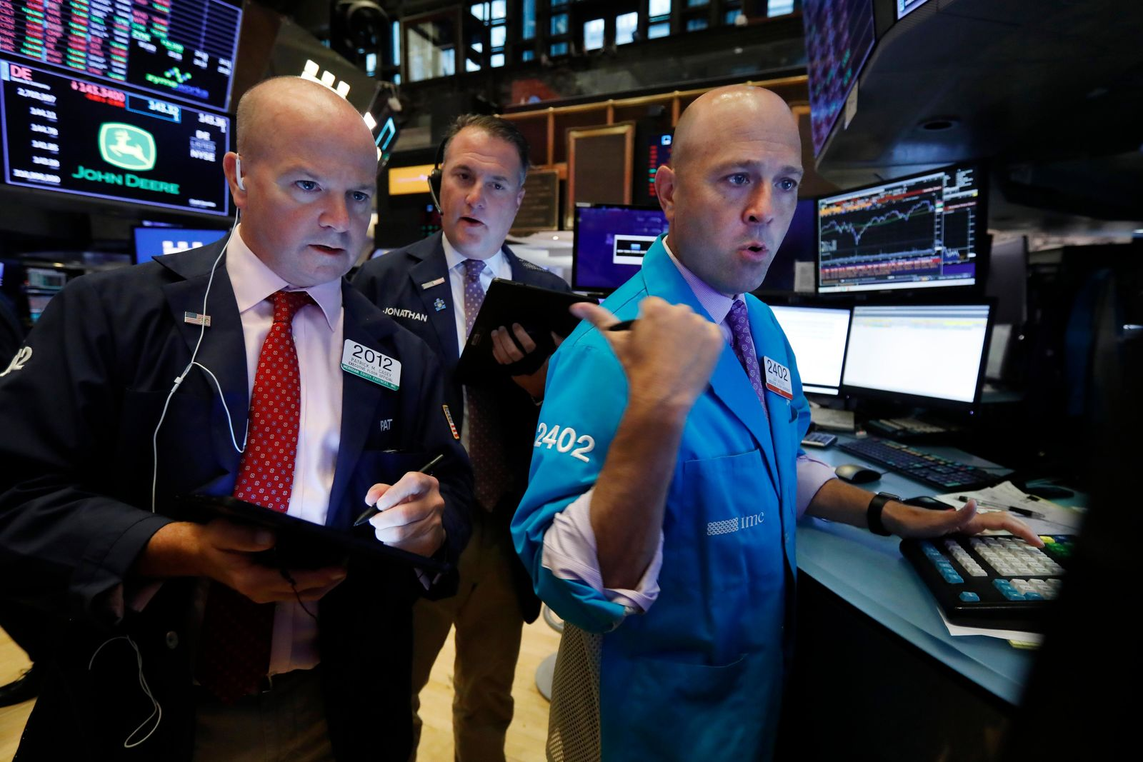 Traders Patrick Casey, left, and Jonathan Corpina, center, work with specialist Jay Woods on the floor of the New York Stock Exchange, Wednesday, Aug. 14, 2019. a warning sign about a possible recession for the first time since 2007. (AP Photo/Richard Drew)
