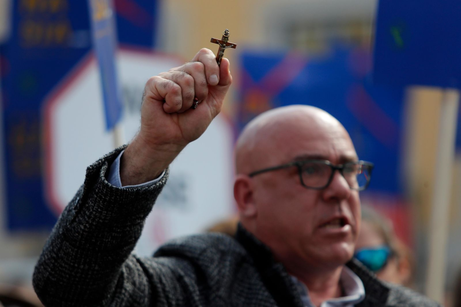 A demonstrator holds a crucifix during a protest outside the Portuguese parliament in Lisbon, Thursday, Feb. 20, 2020. (AP Photo/Armando Franca)