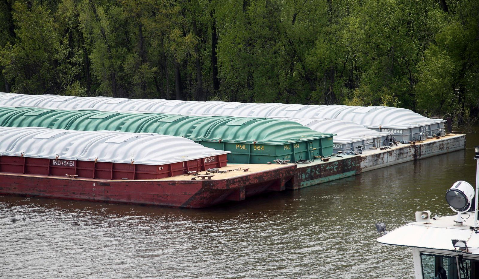 In this Tuesday, May 14, 2019 photo, barges already loaded with soy beans, potash or scrap steel await movement on the Mississippi River in St. Paul, Minn., as spring flooding interrupts shipments on the river. (AP Photo/Jim Mone)